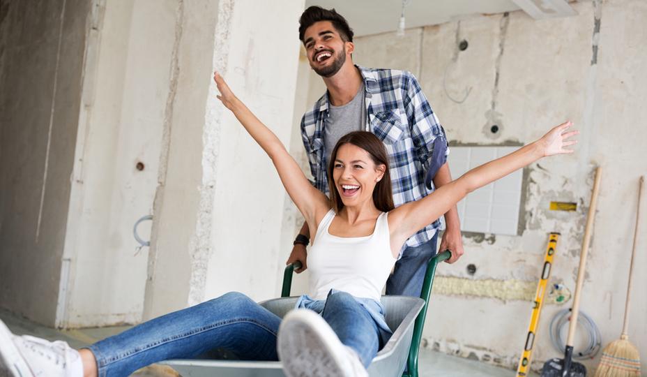homme poussant femme dans une brouette sur un chantier de rénovation