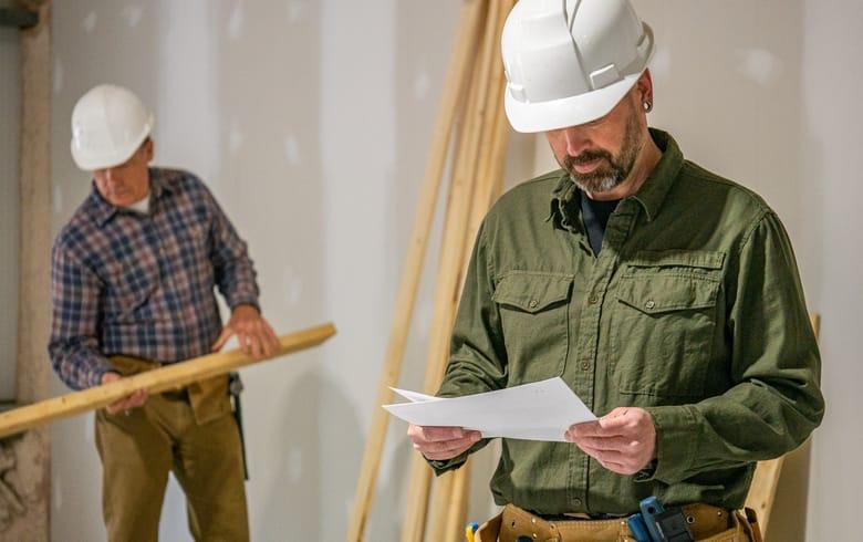 2 entrepreneurs avec casques blancs travaillants sur un chantier