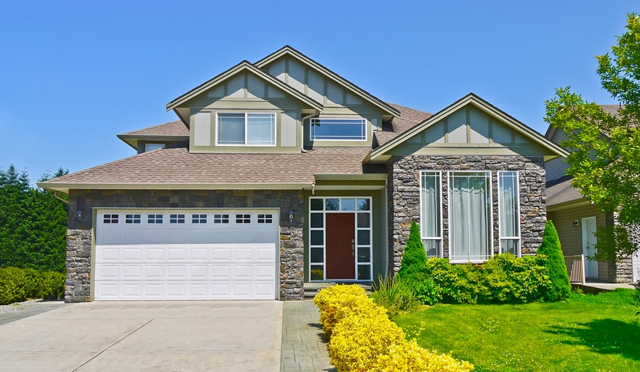 extérieur maison en pierre naturelle avec porte de garage simple blanche