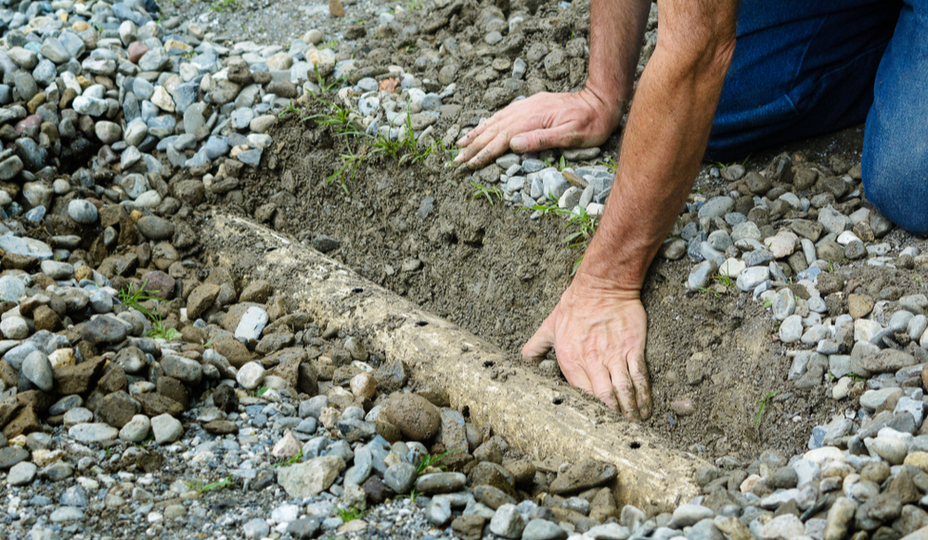 Homme procédant à l'installation d'un drain français