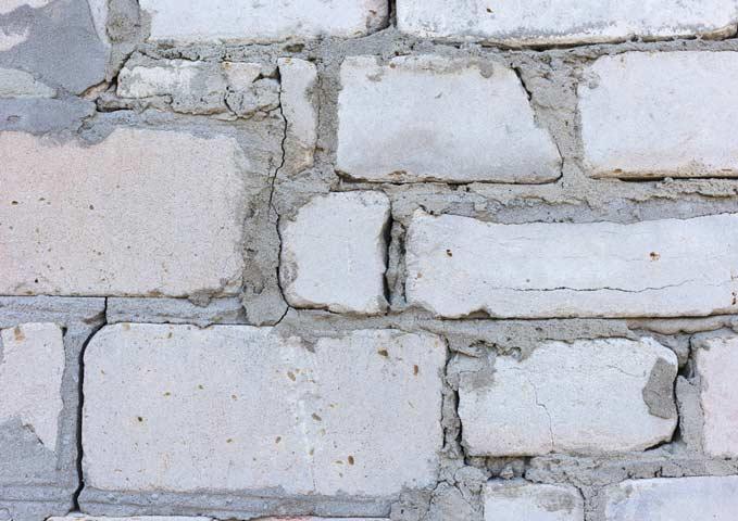 mur de brique endommagé avec fissures
