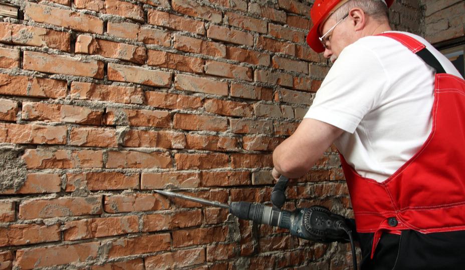 homme effectuant un rejointoiement de briques avec une machine