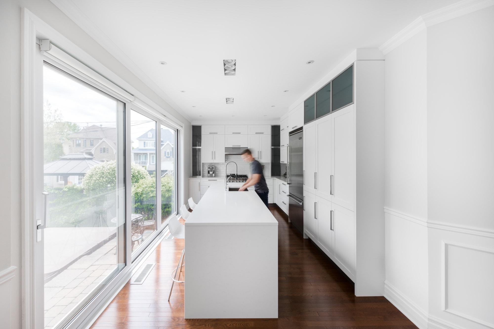 rénovation d'une cuisine moderne blanche avec grans îlot et comptoirs de quartz blancs