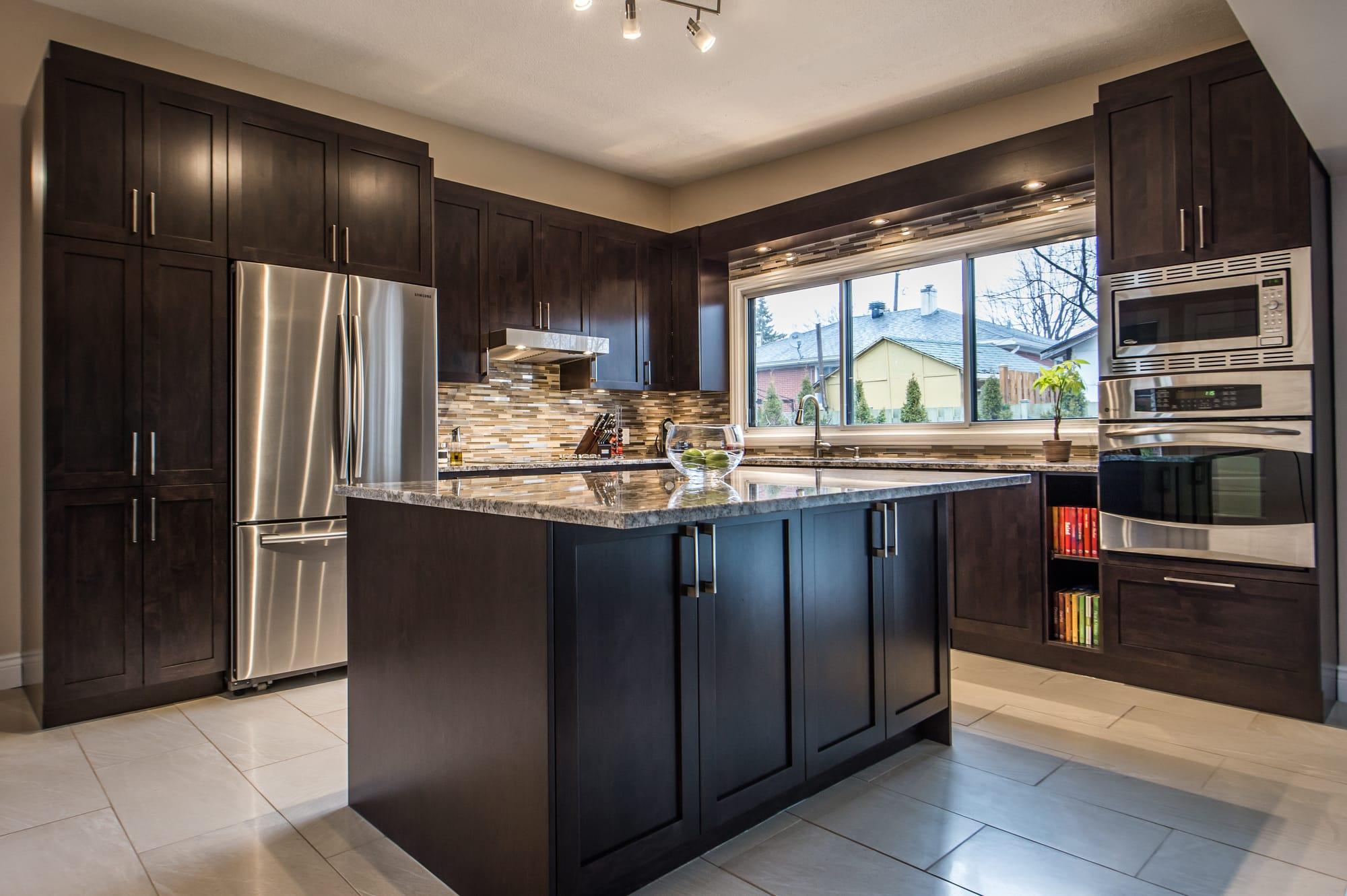 cuisine moderne en bois foncé de style shaker avec îlot, comptoirs de granite et four encastré