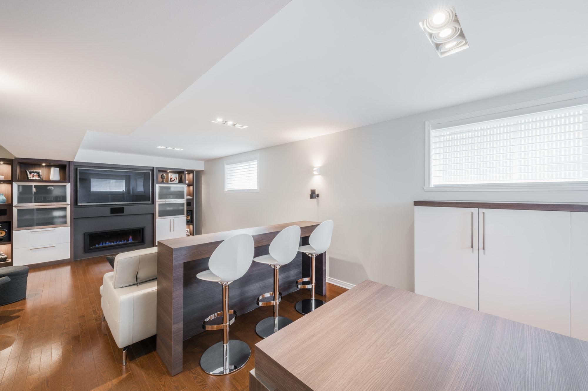 aménagement de sous-sol avec comptoir lunch et meubles sur mesure - Style contemporain