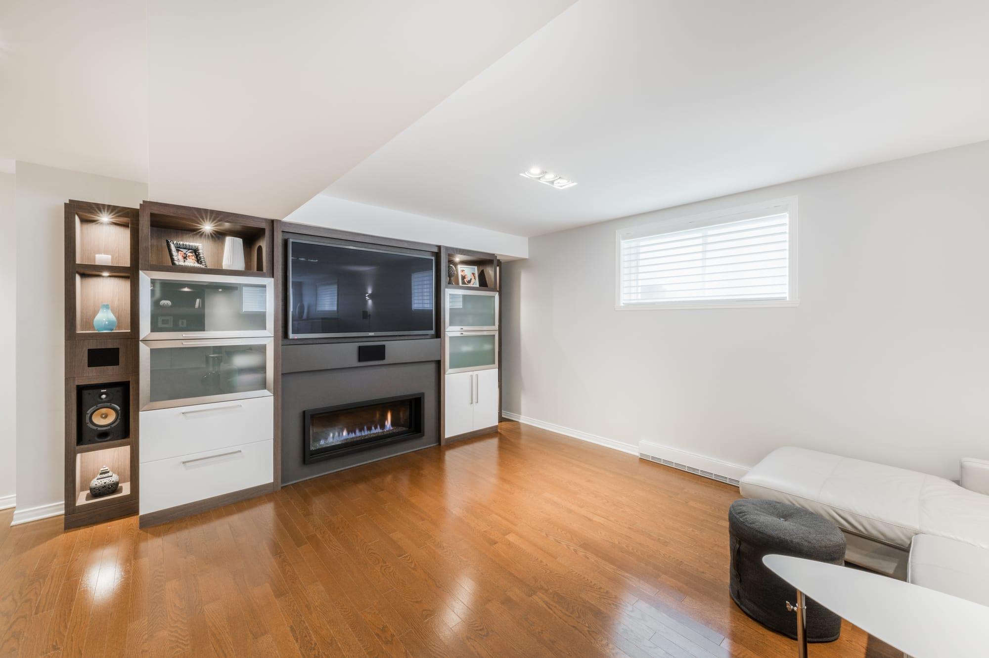 décoration de sous-sol avec meuble de télé fait sur mesure avec foyer au gaz
