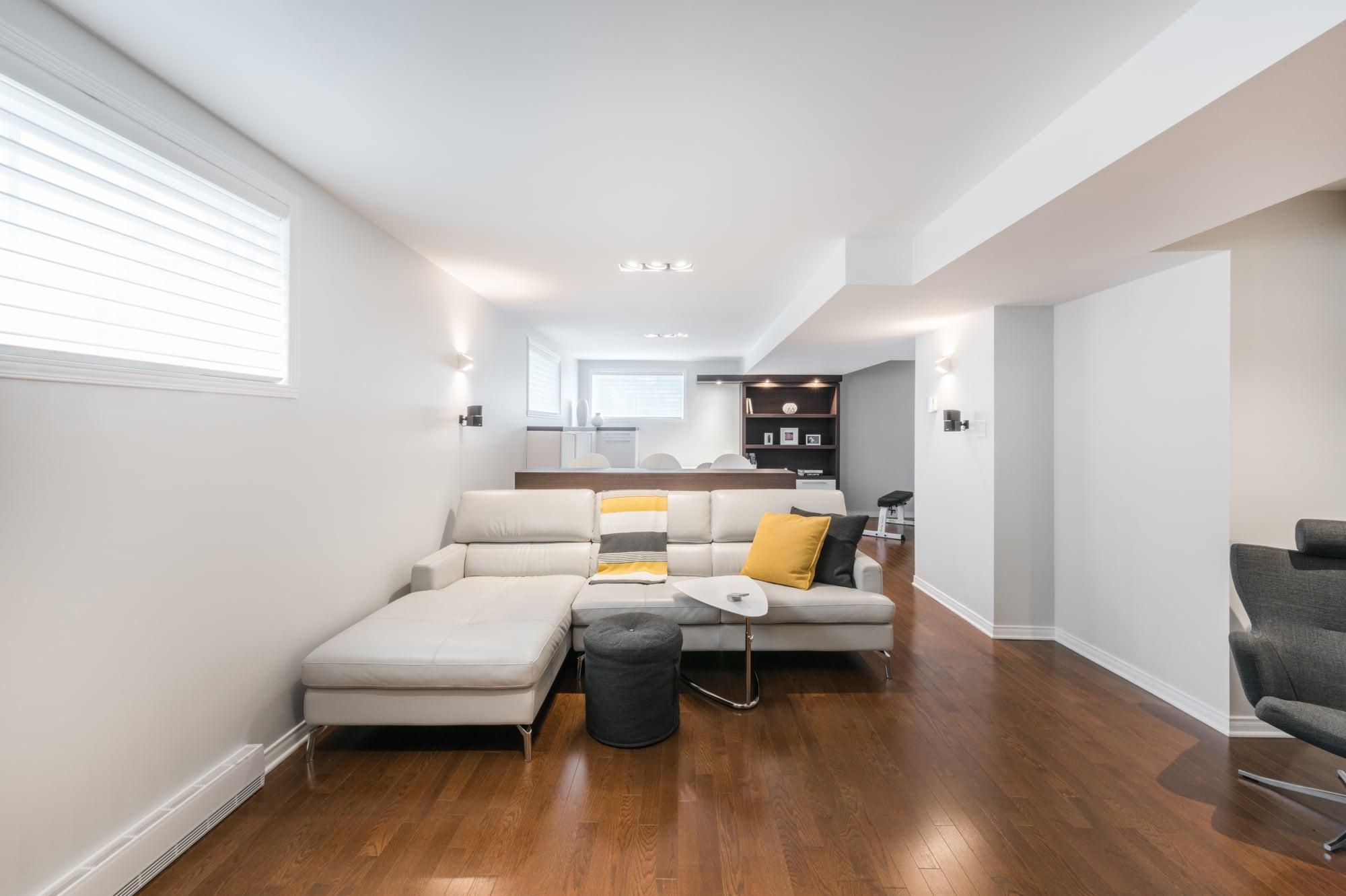 rénovation d'un sous-sol de style contemporain avec divant beige et plancher de bois franc