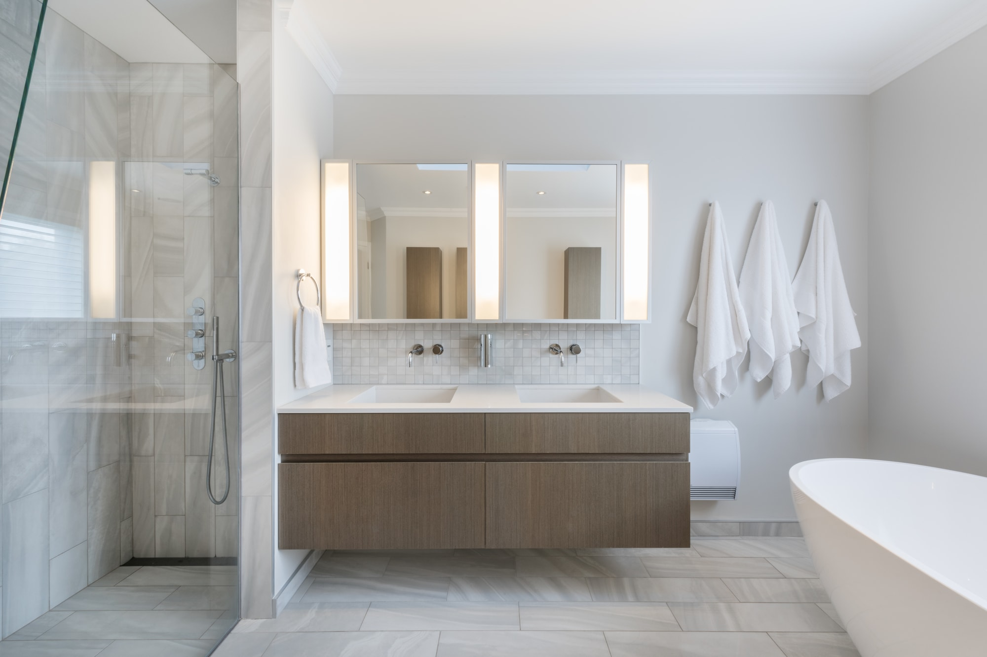 modern renovated bathroom with double sinks, glass shower, and standing bath