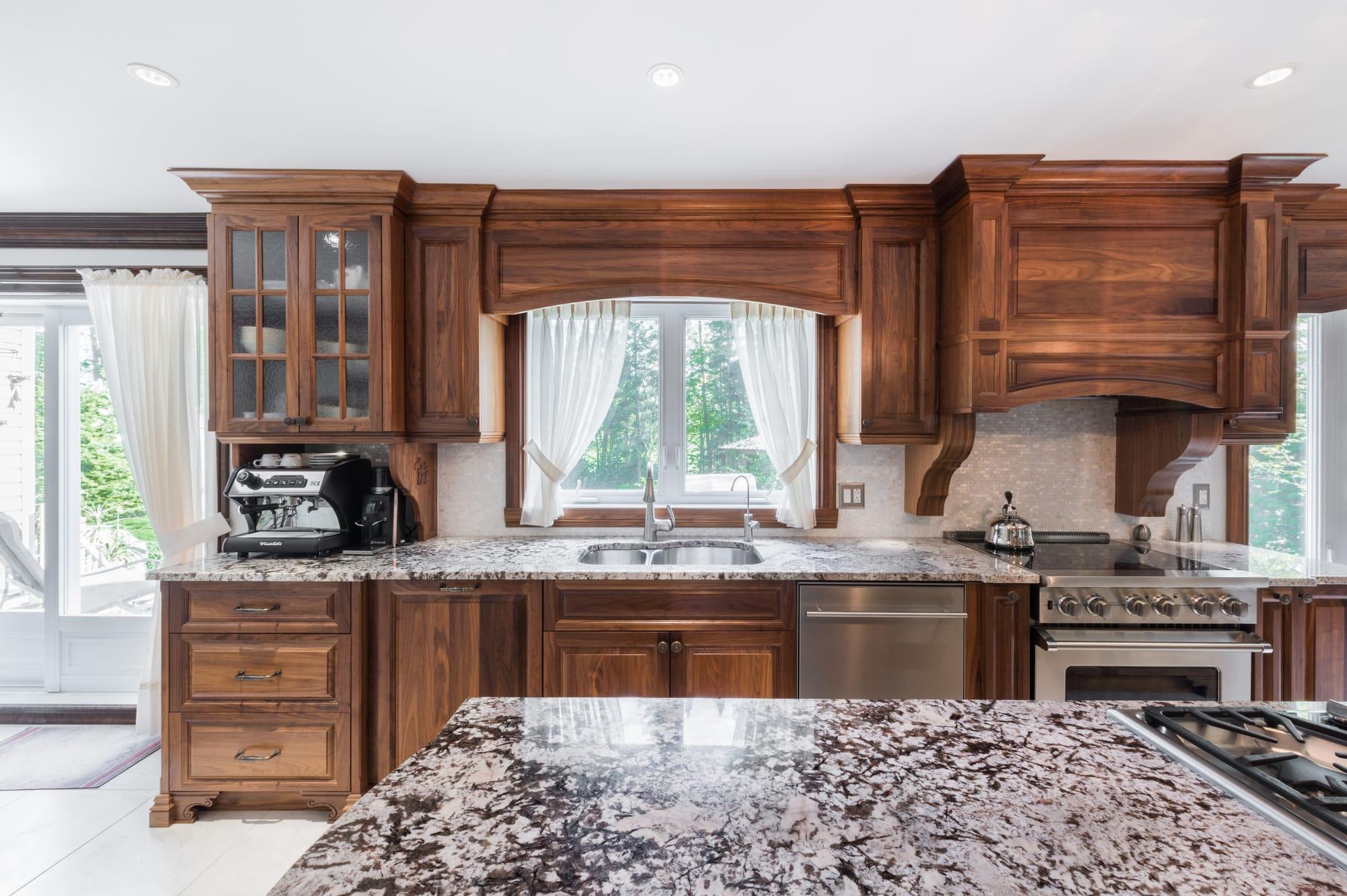 cuisine design de style classique en noyer foncé, grand îlot et comptoirs de granite