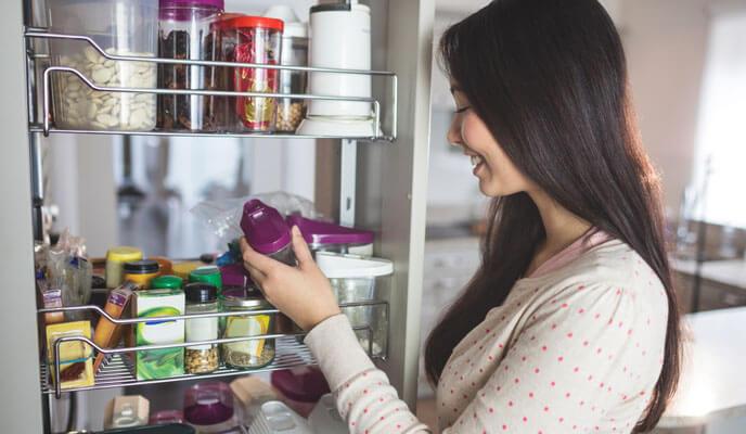 Jeune femme dans une cuisine devant garde-manger coulissant