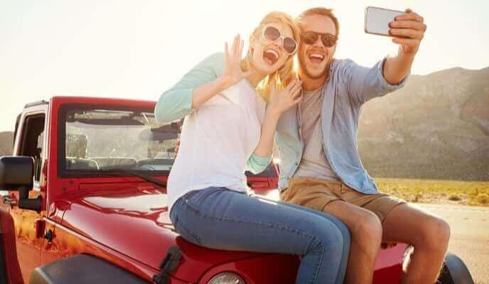 couple assis sur jeep rouge se prenant en photo en voyage