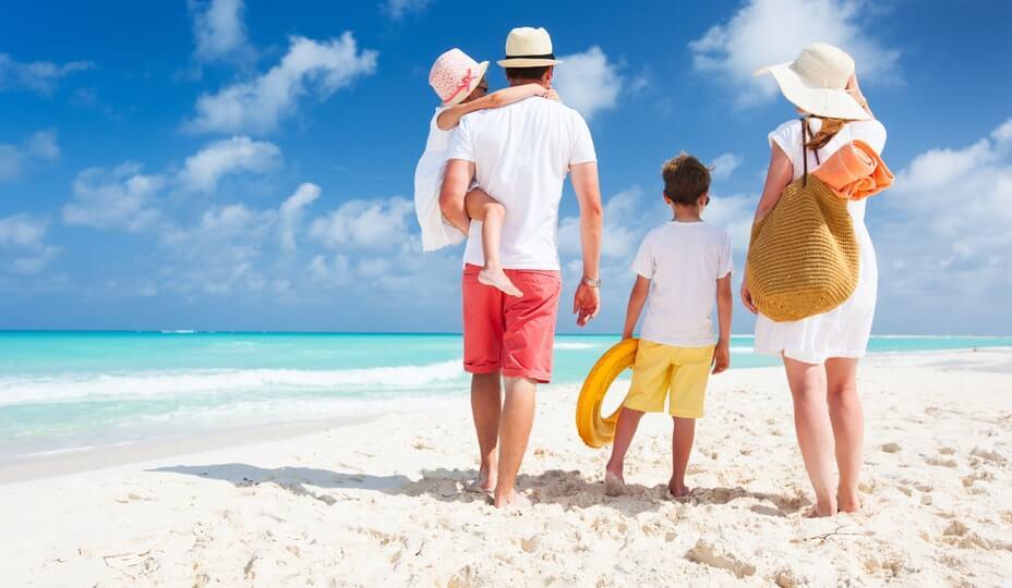 jeune famille de quatre sur la plage vue de dos