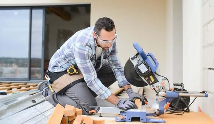 Contracteur en train utilisant scie circulaire pour construction d'un balcon en bois