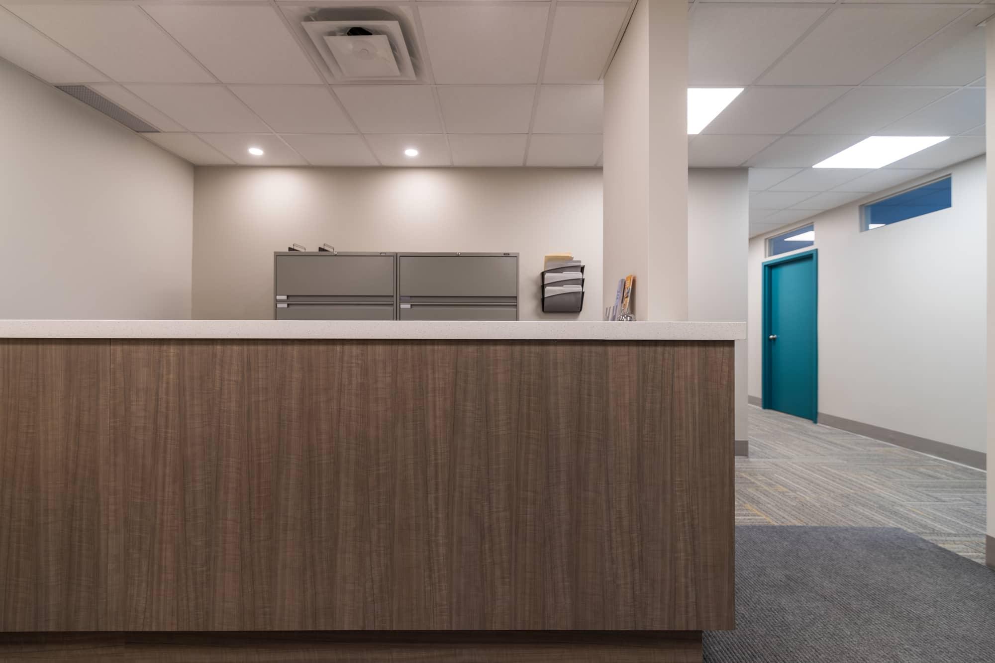Comptoir de réception d'une clinique de physiothérapie donnant sur corridor avec porte turquoise