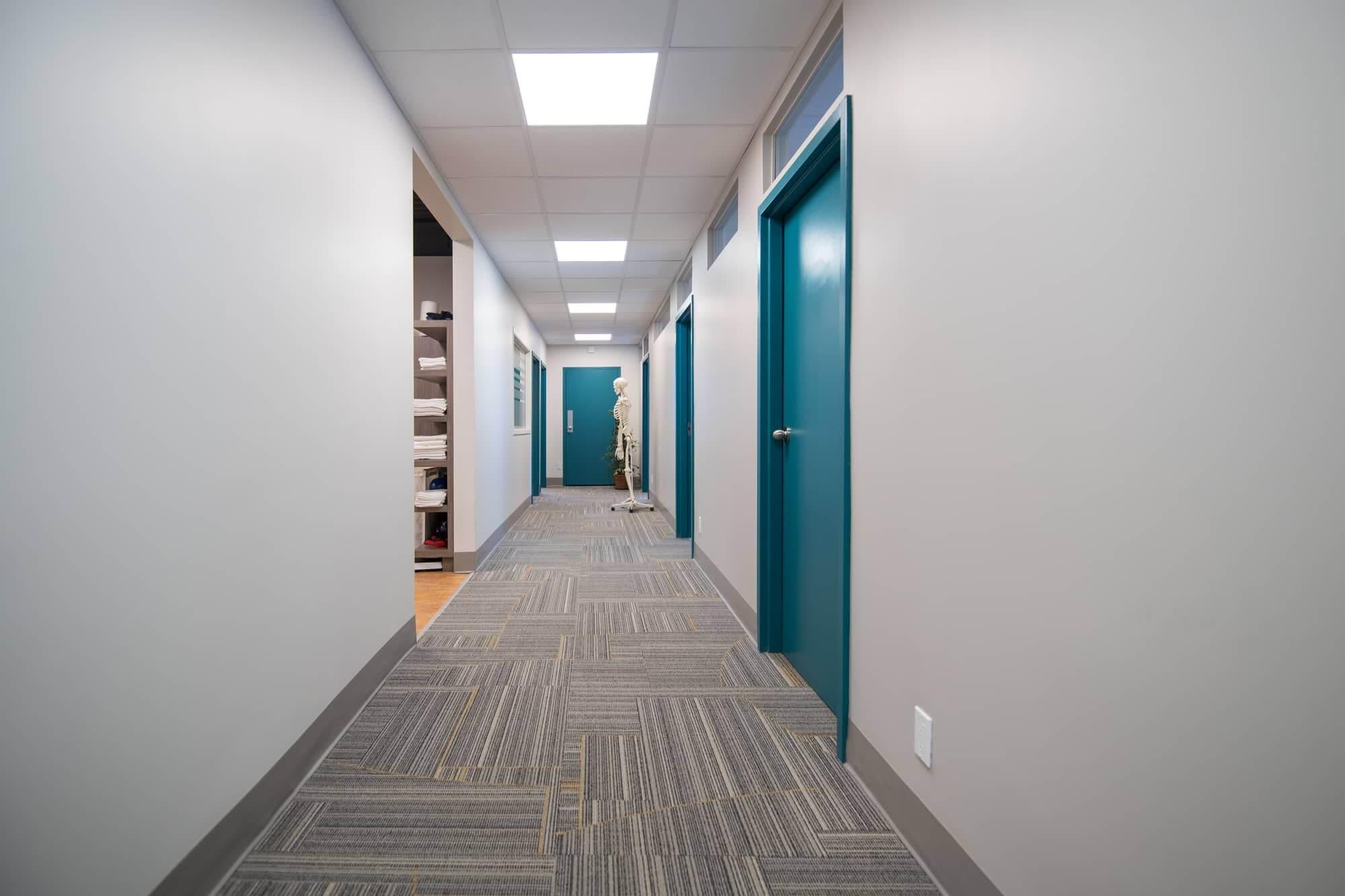 Corridor d'une clinique de physiothérapie avec portes turquoises et beau tapis commercial (nouvellement aménagée)