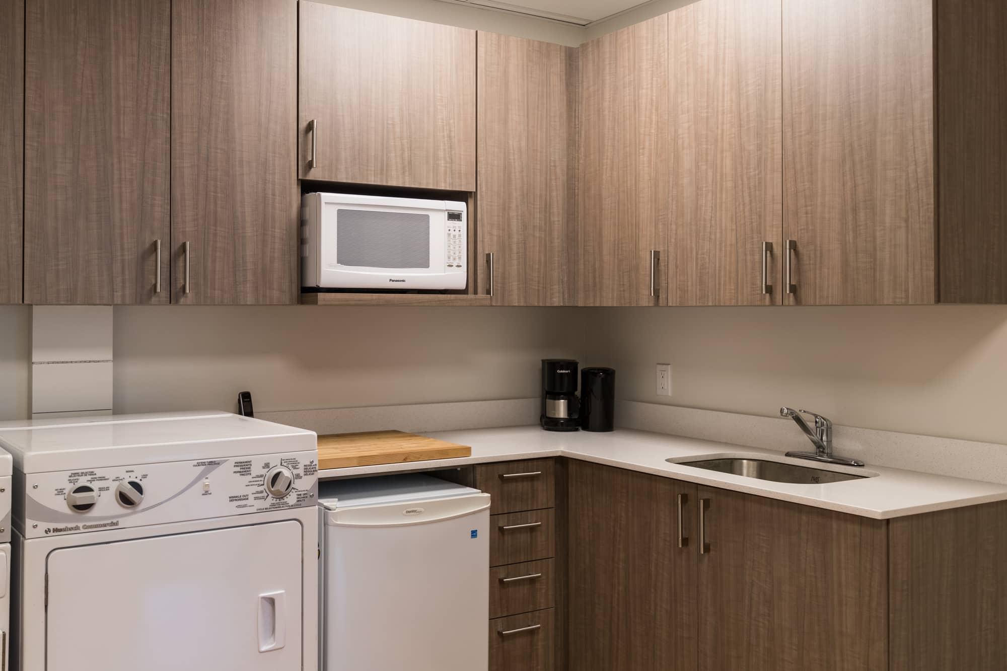 Salle d'employés rénovée avec laveuse, mini-frigo, micro-ondes, lavabo et armoire en mélamine brun pâle