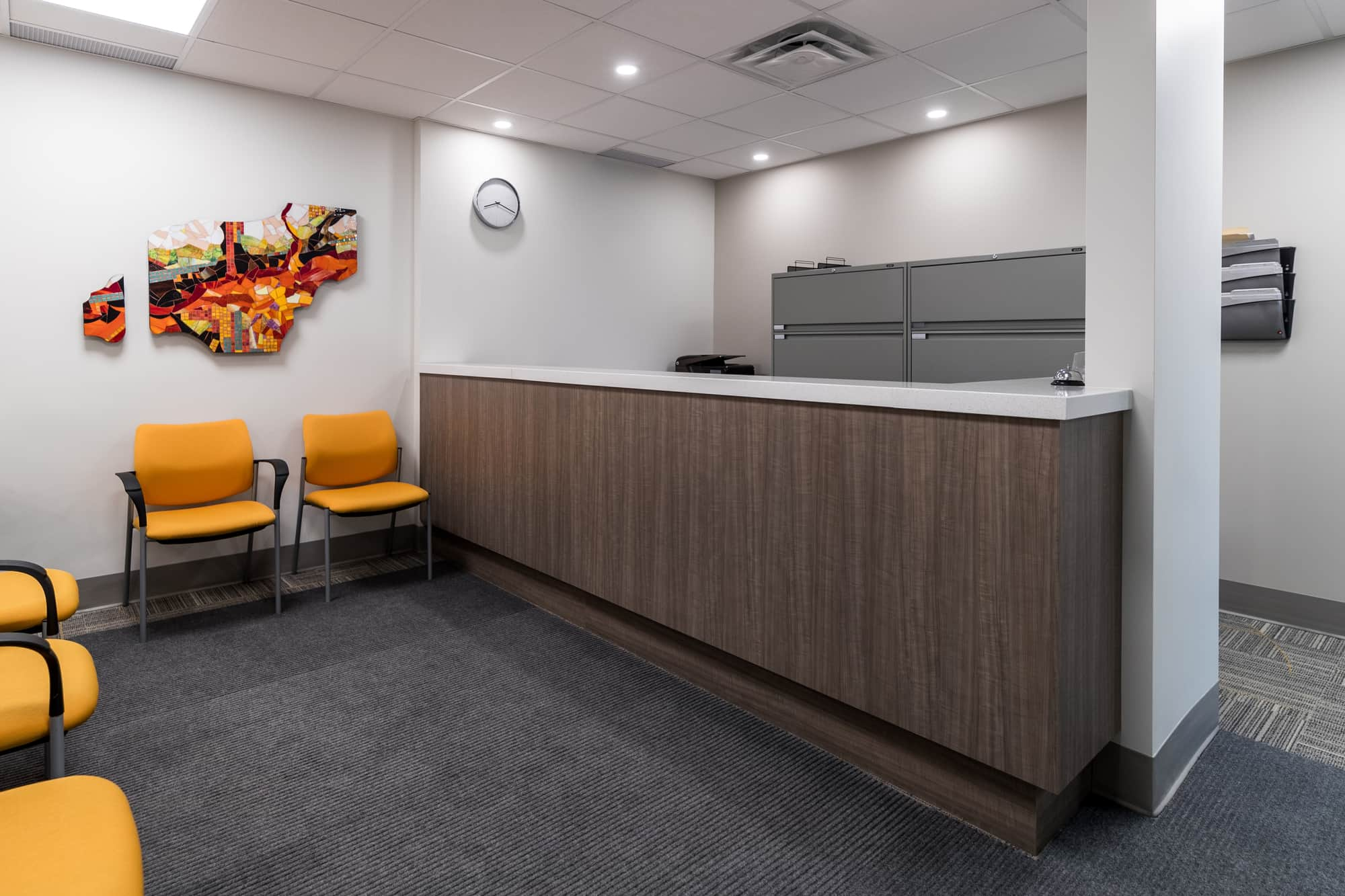 Grey reception desk with yellow chairs in a physiotherapy clinic newly renovated