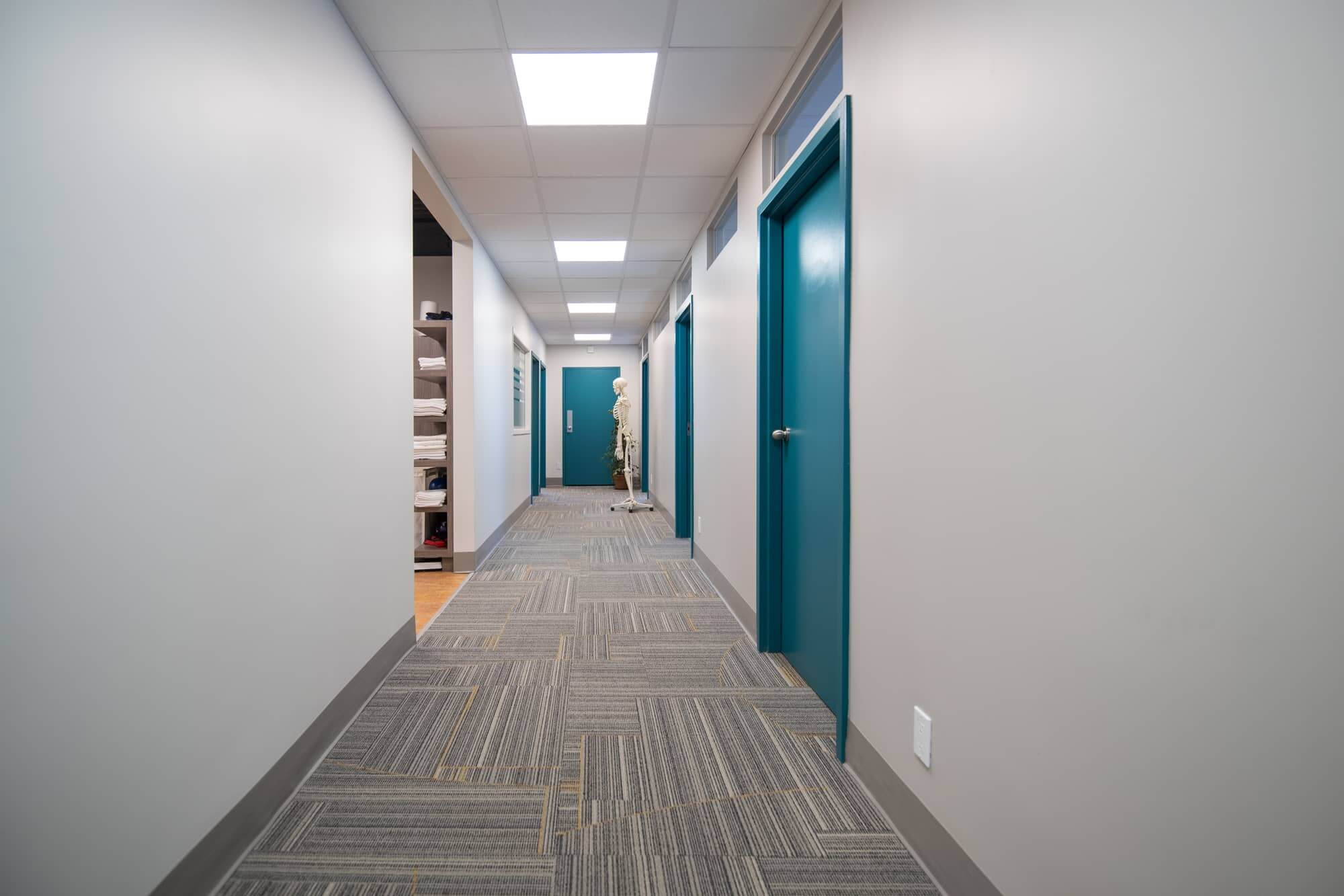 New corridor with commercial carpet and turquoise doors in a clinic