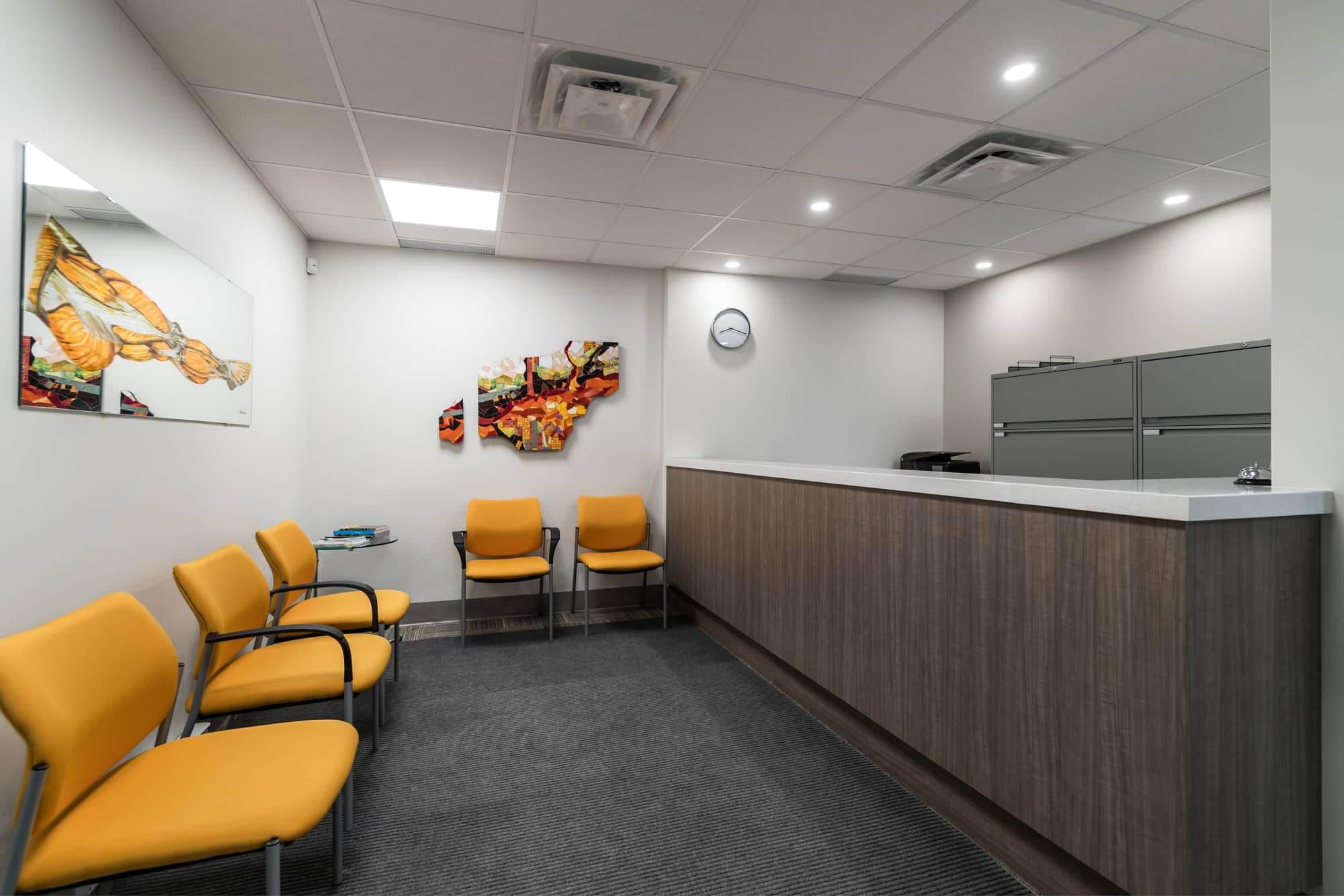 Nouvelle salle d'attente rénovée dans une clinique de physiothérapie avec chaises jaune moutarde donnant sur la réception