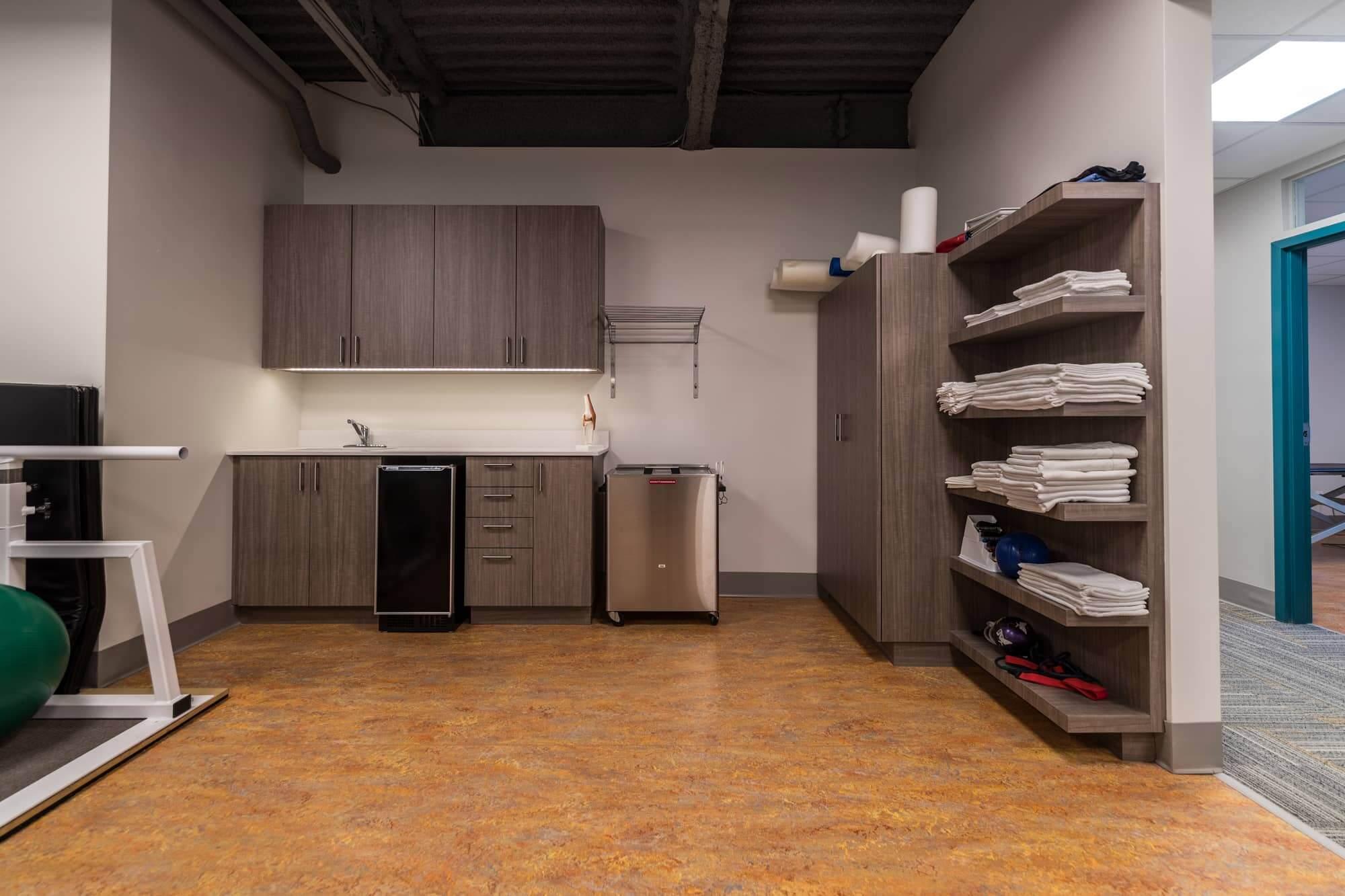 Salle de réadaptation d'une clinique de physiothérapie avec armoires et rangements étagés