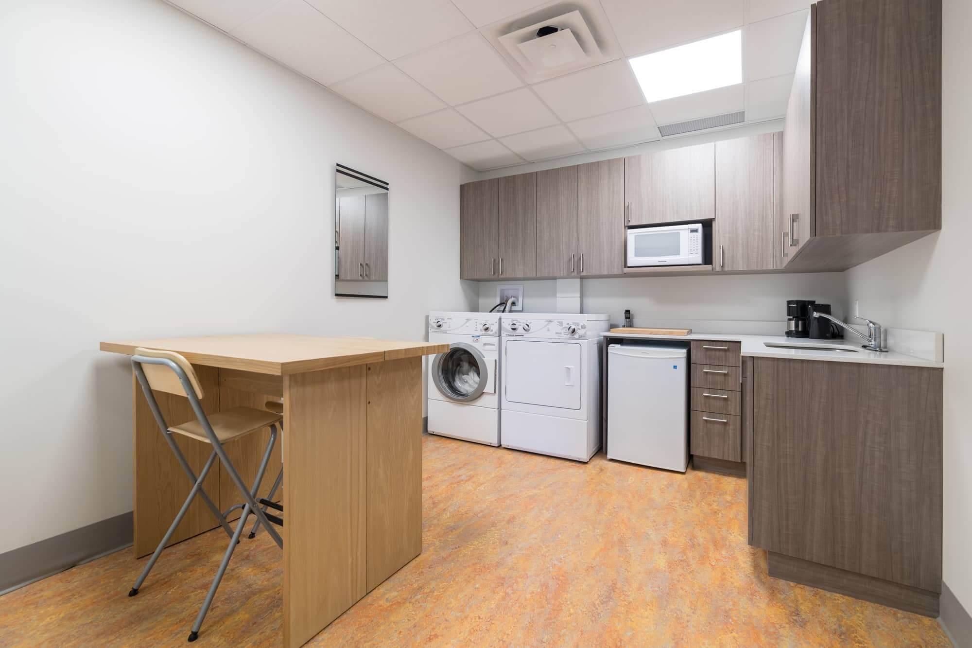 Salle d'employés avec laveuse, sécheuse, comptoir et lavabo