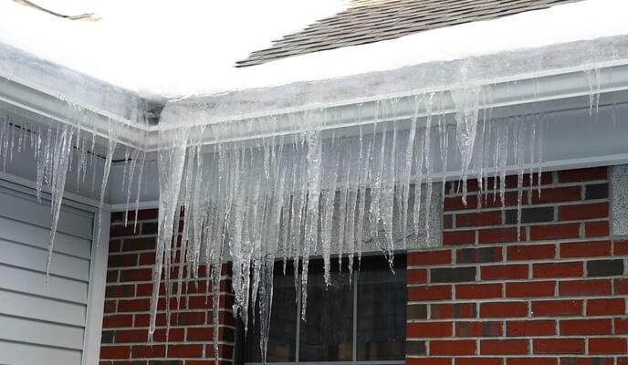 Glaçons accrochés à la toiture d'une maison en brique rouge - Problème ventilation toiture