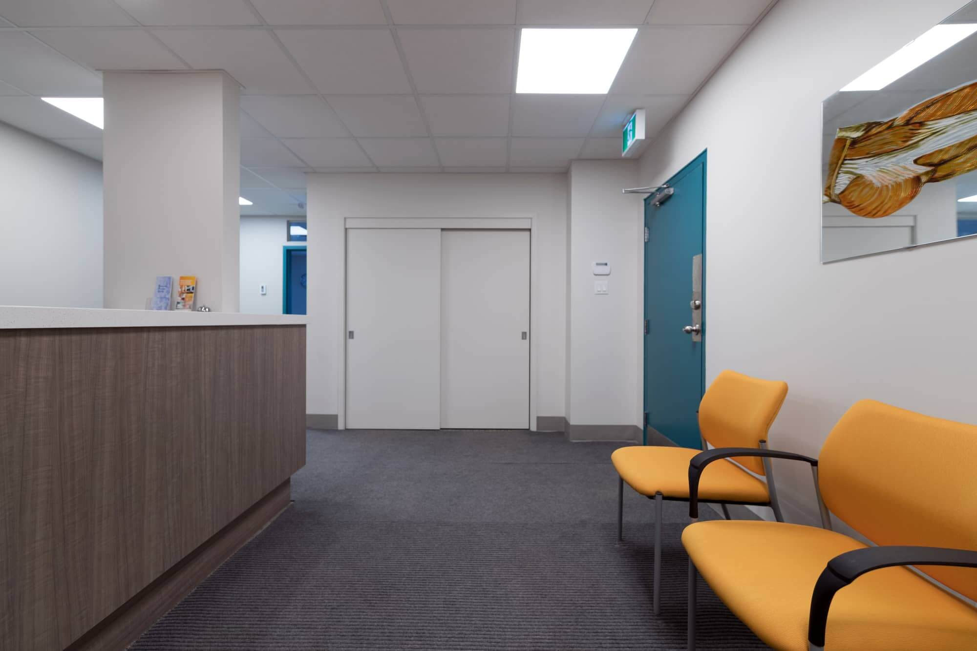 Waiting room with yellow chairs and turquoise door in a physiotherapy clinic newly renovated