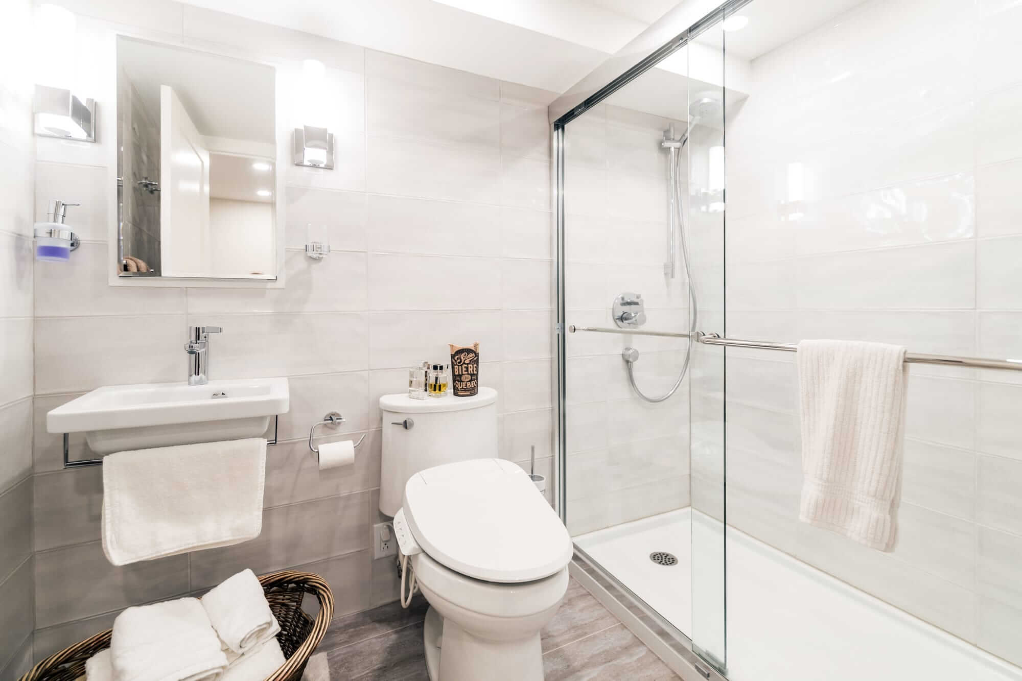 Modern basement bathroom with freestanding white washbasin and a shower bath