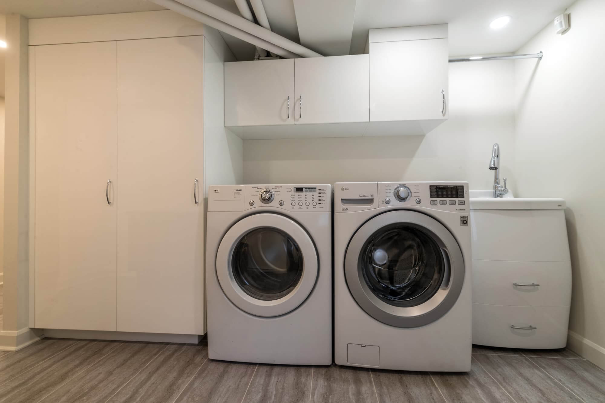 Laundry room in a newly renovated basement with white custom cabinets and washer/dryer