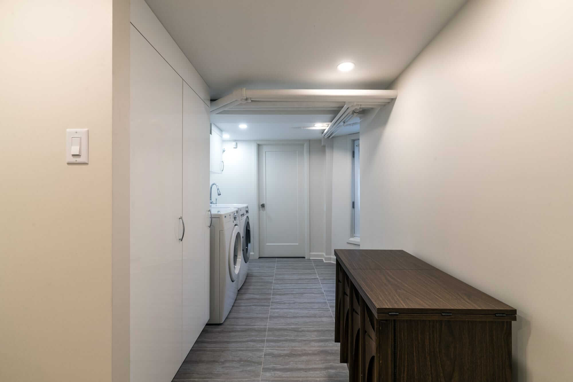 Basement laundry room with wooden furniture