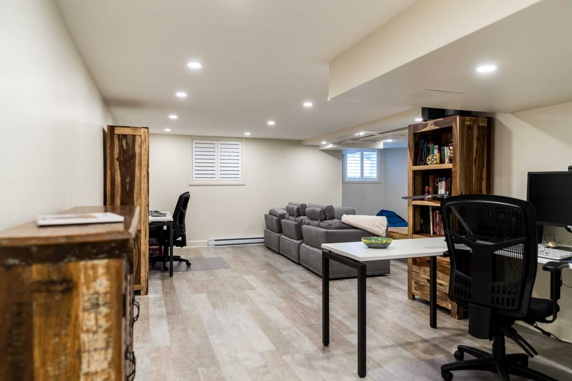 Basement renovation with grey floating floor, beige walls and wooden furniture