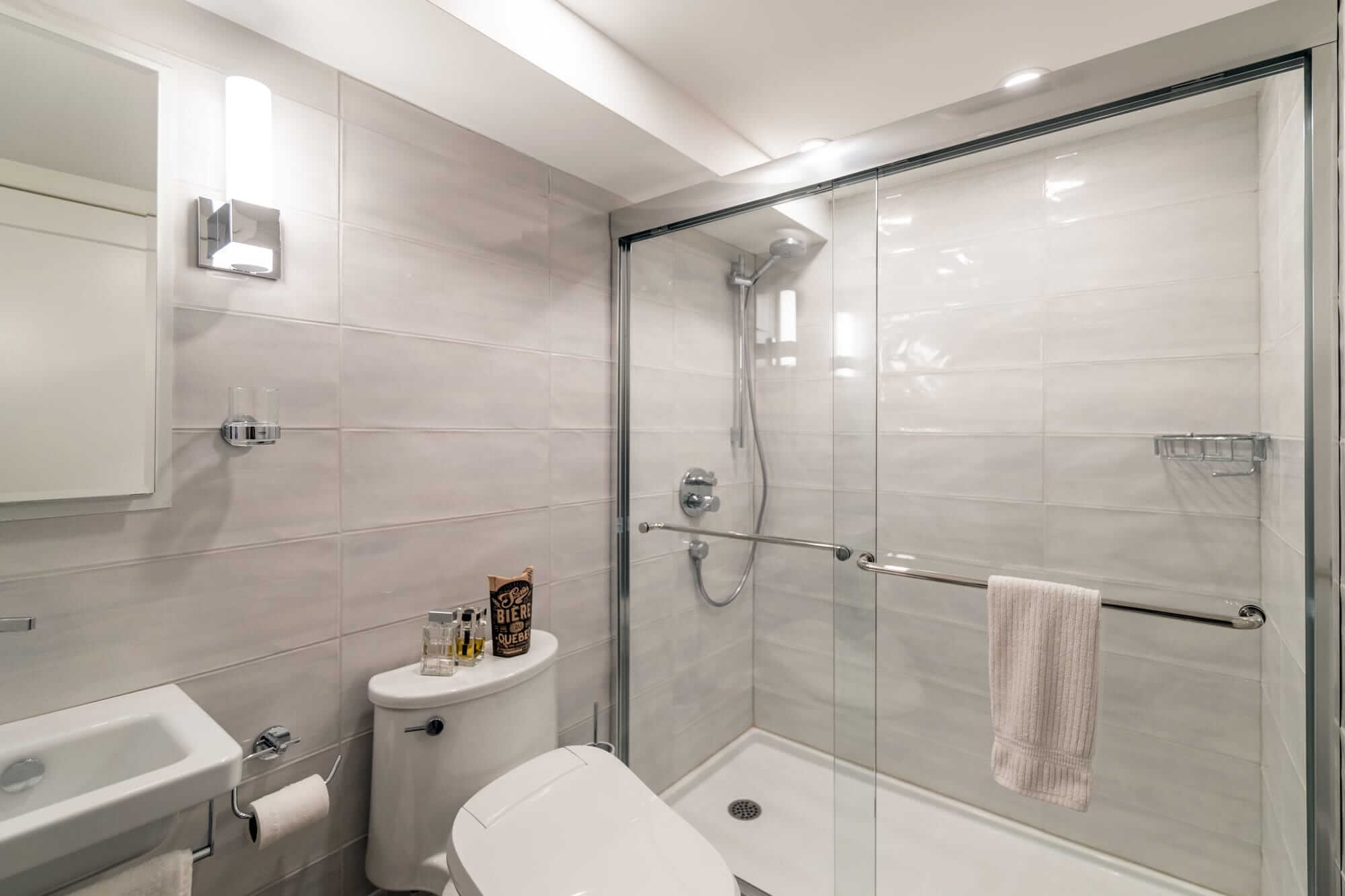Contemporary bathroom in a basement with shower bath and white freestanding washbasin