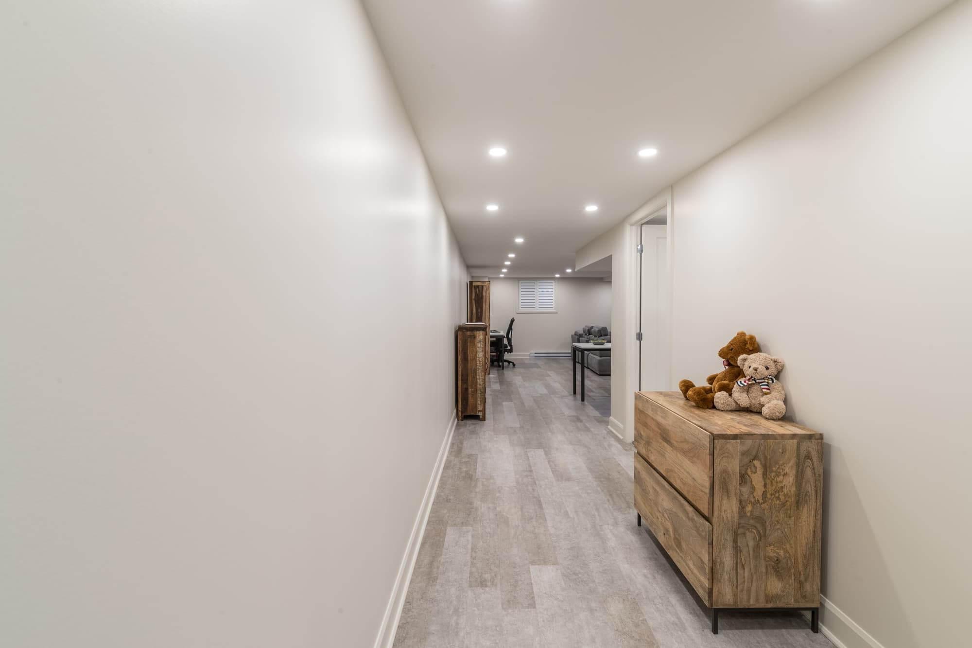 Corridor d'un sous-sol moderne rénovée avec murs sable, meuble en bois, plancher flottant gris pâle et éclairage encastré