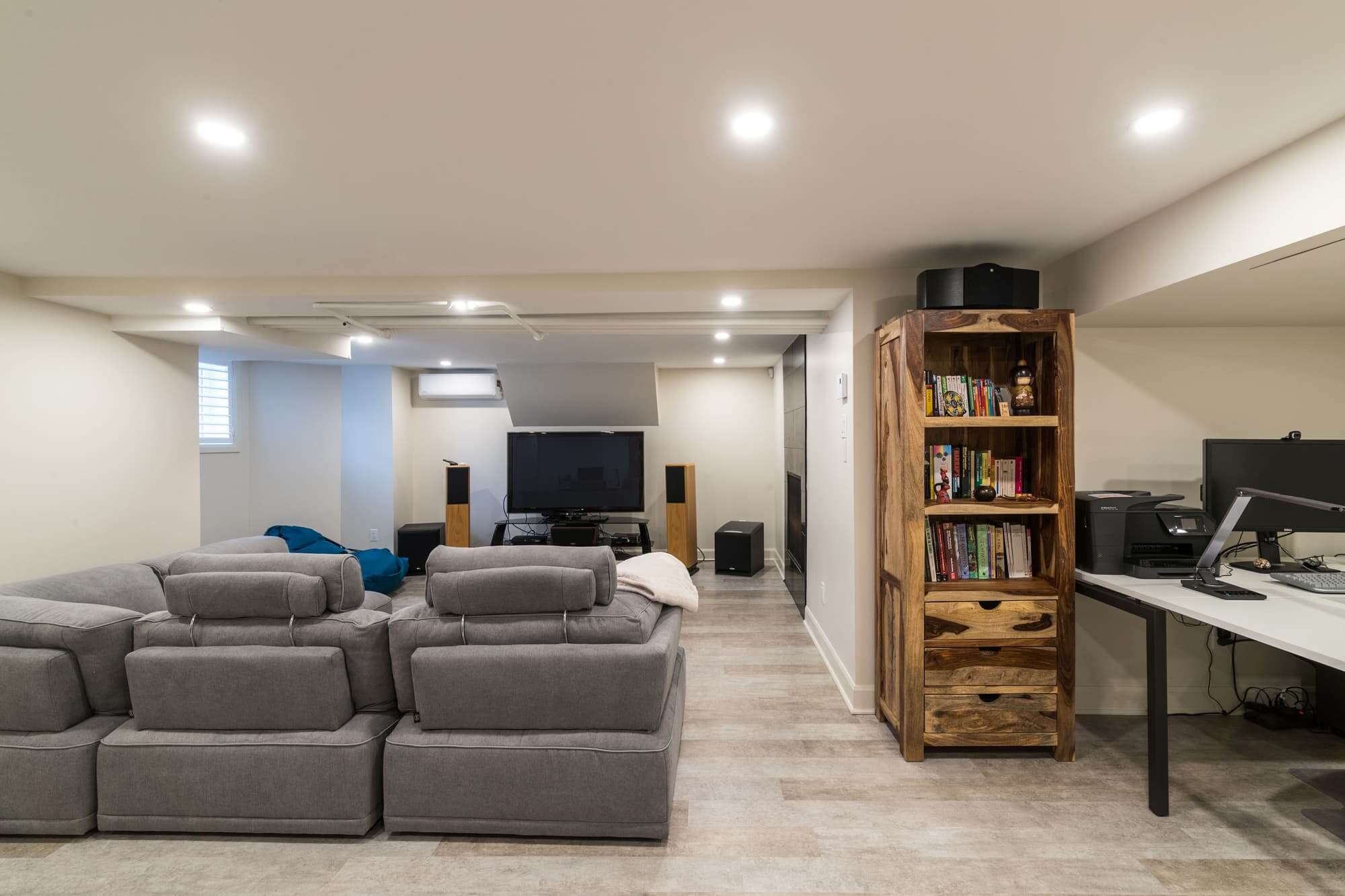 Family room in a basement with fireplace, grey sofa, office area and wooden furniture