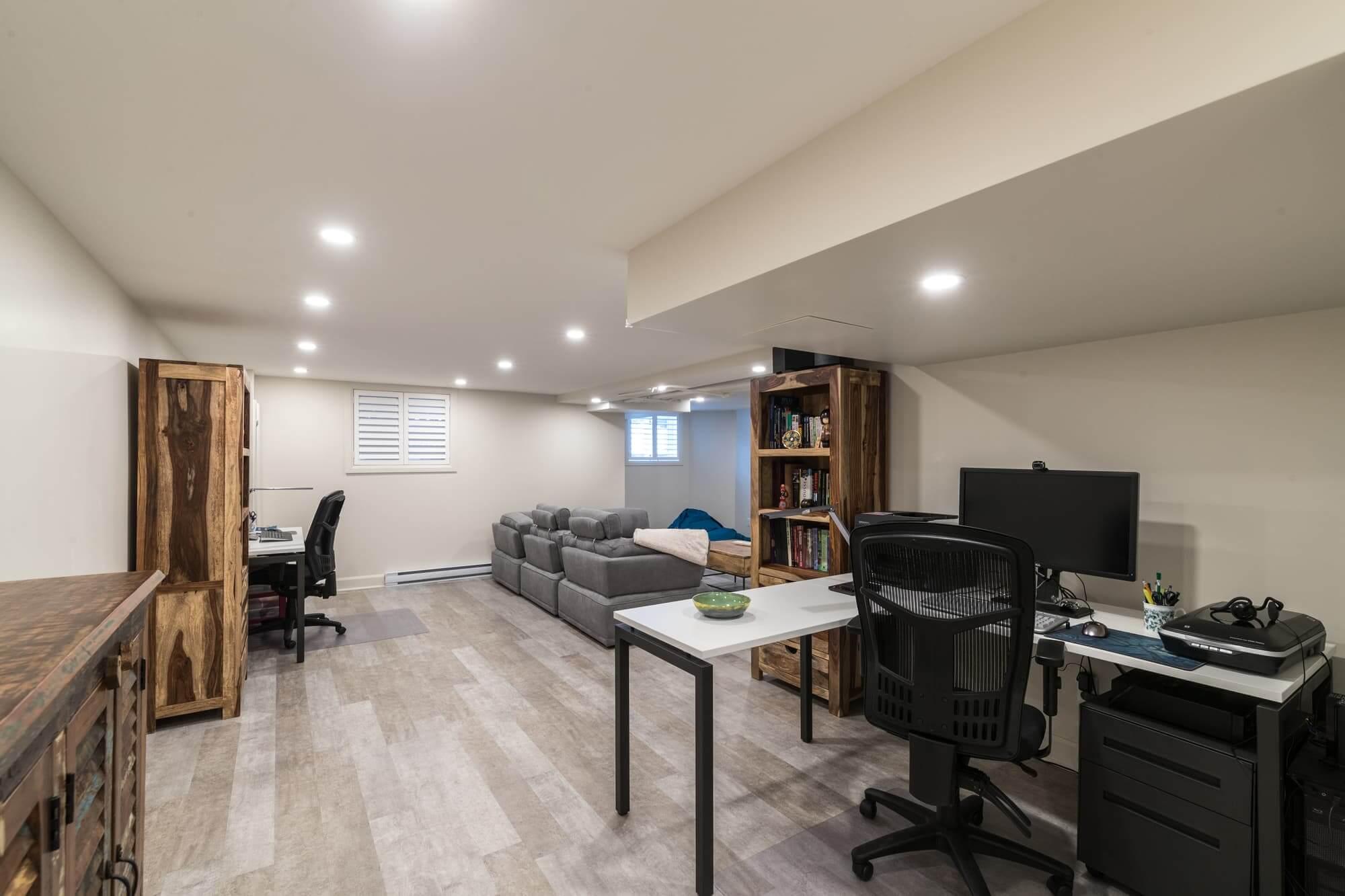 Rénovation d'un sous-sol moderne avec coin bureau et plancher en bois flottant gris pâle
