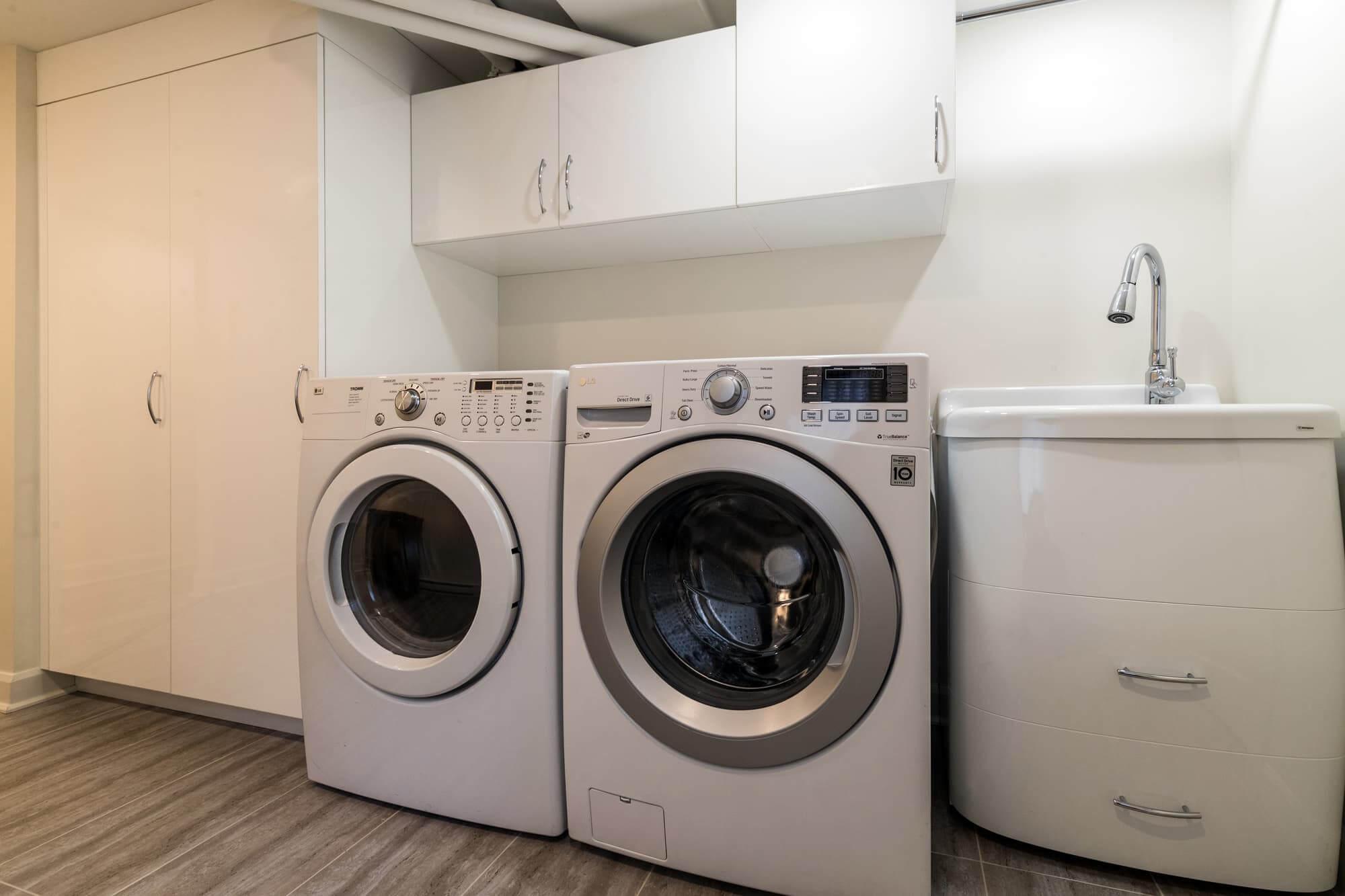 Salle de lavage d'un sous-sol rénové avec laveuse-sécheuse frontales et lavabo blanc
