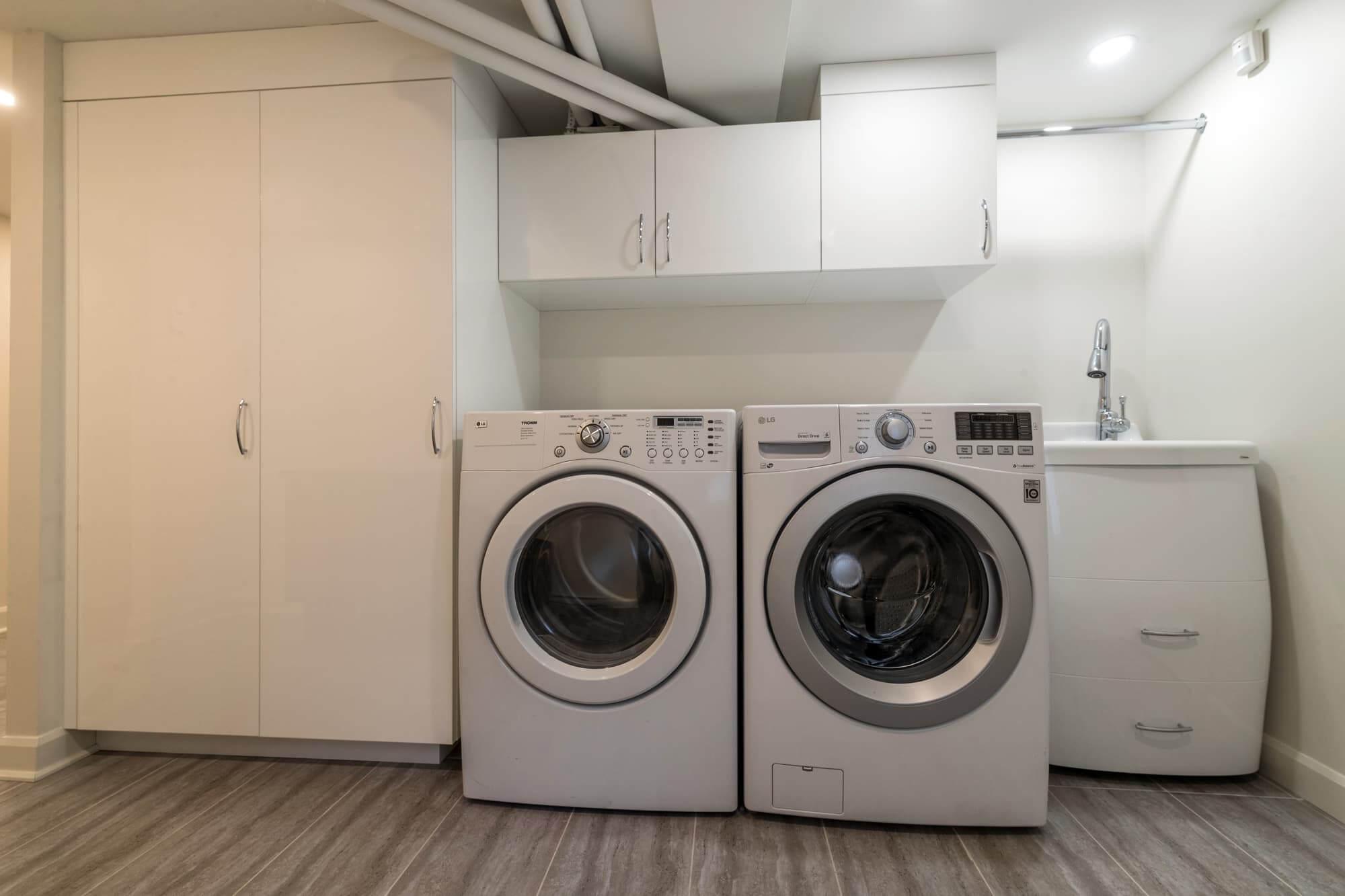 Salle de lavage dans un sousl-sol rénové avec une amoire blanche murale, un lavabo blanc et laveuse-sécheuse frontales