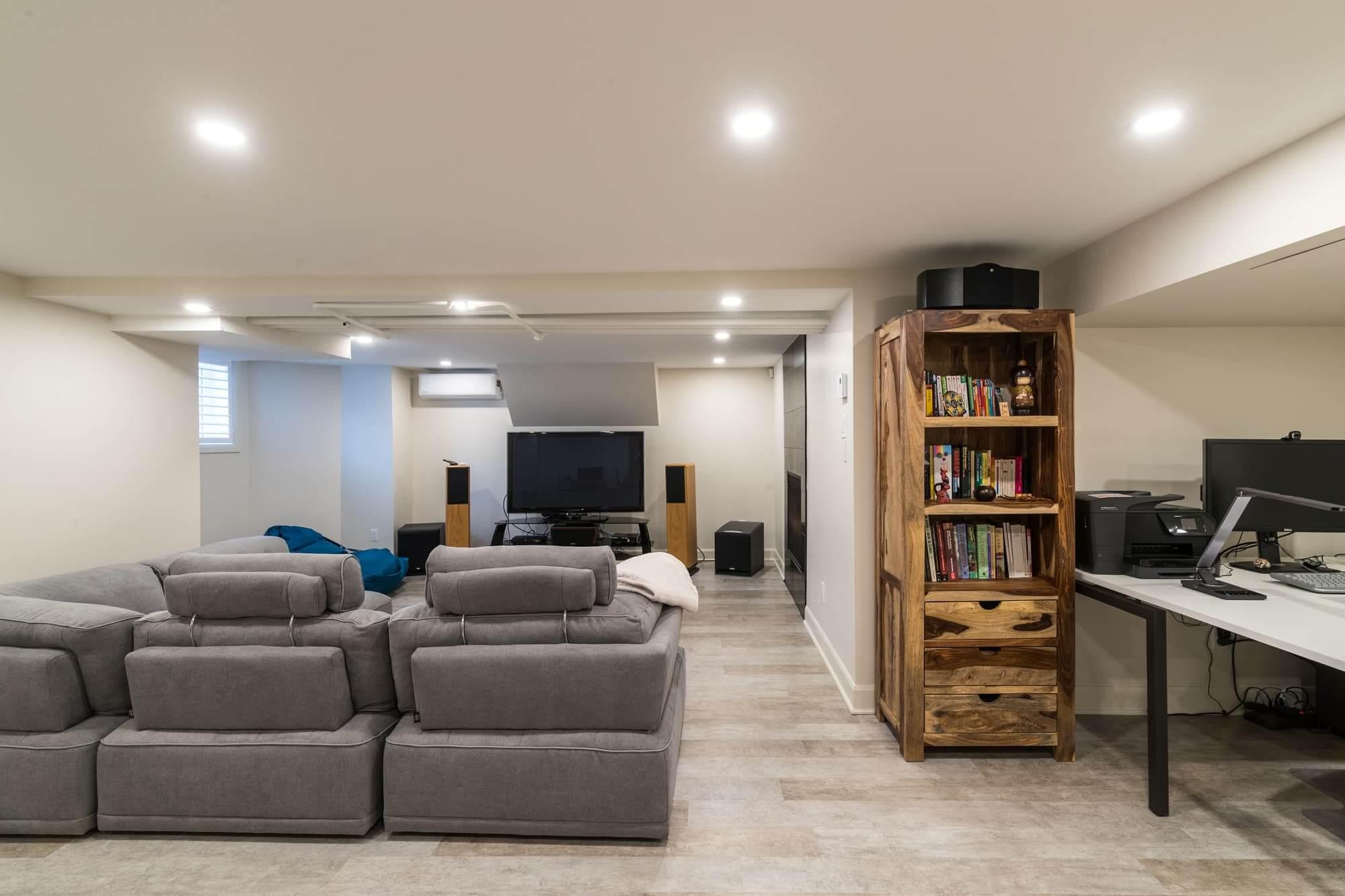 Salle familiale d'un sous-sol rénovée avec divan gris, télé, coin bureau, murs beiges et étagère en bois