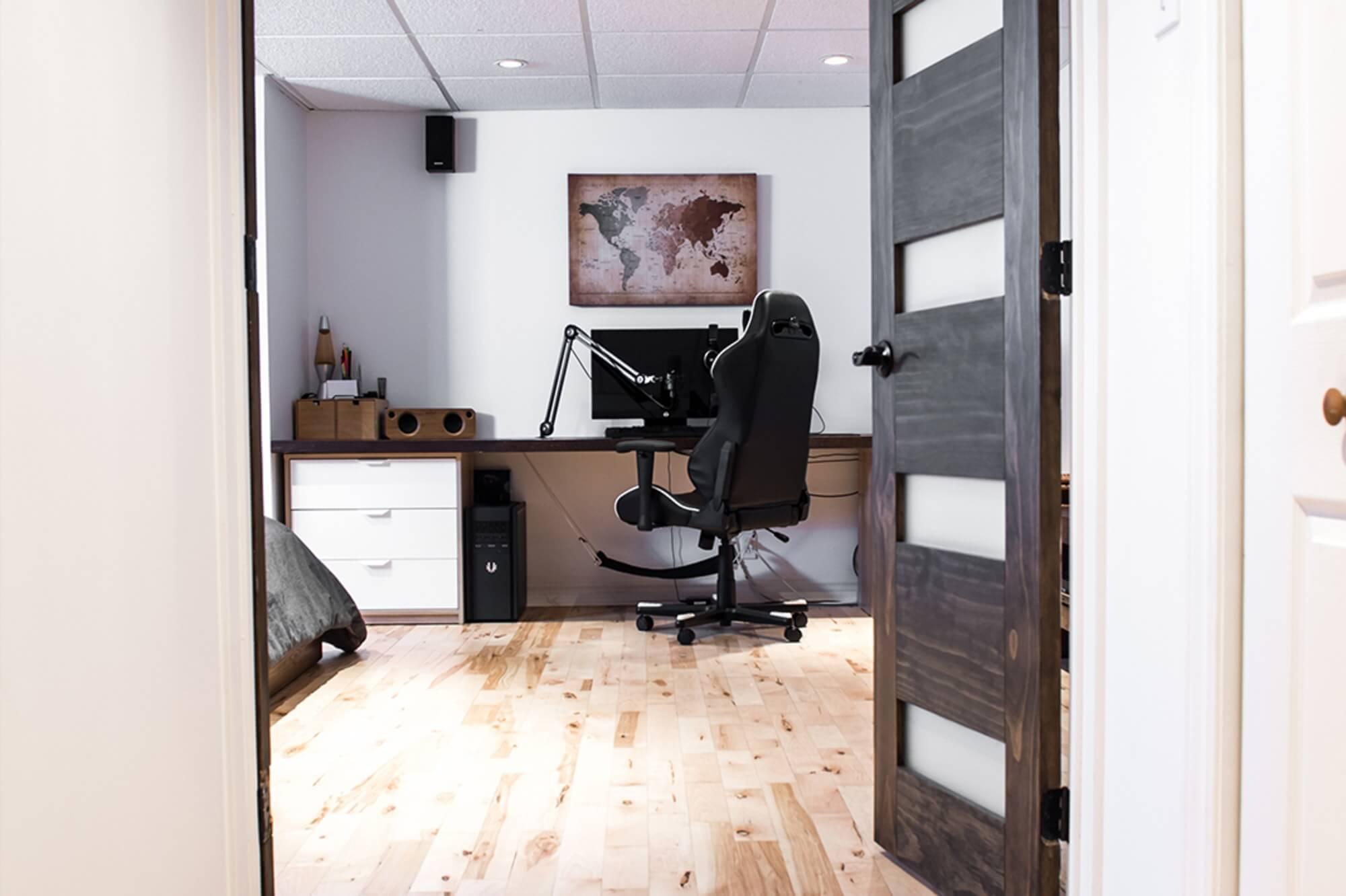 Bureau dans un sous-sol rénovée avec porte en bois brun et plancher de bois franc naturel
