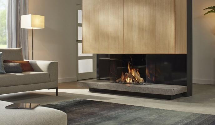 Foyer au bois de Spartherm avec divan en tissu gris pâle et carpette charcoal - SIDIM