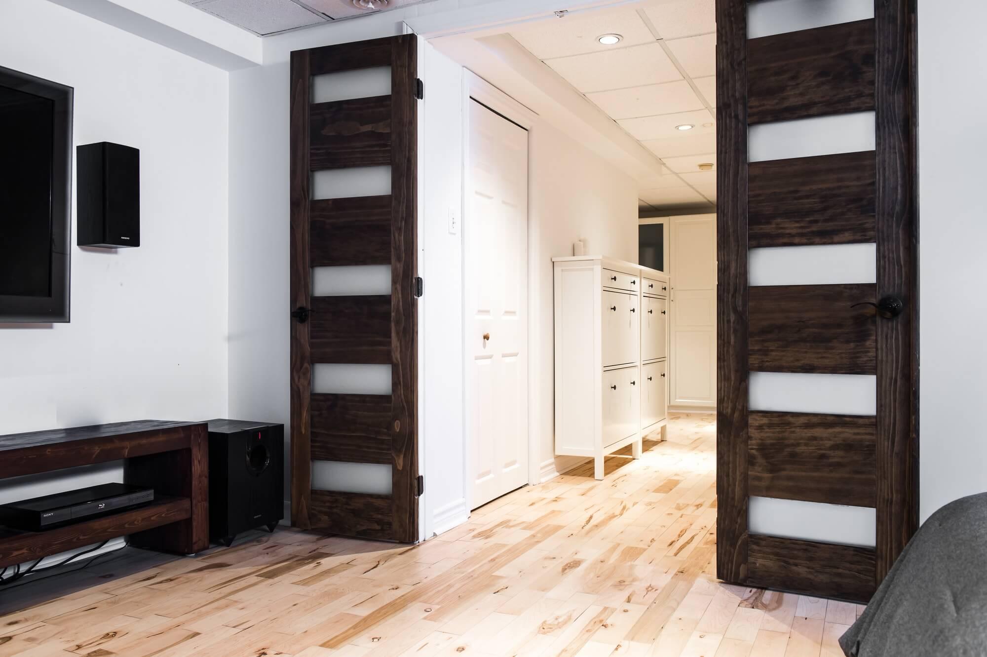 Aménagement de sous-sol avec plancher de bois franc pâle et grandes portes en bois vitrées foncées