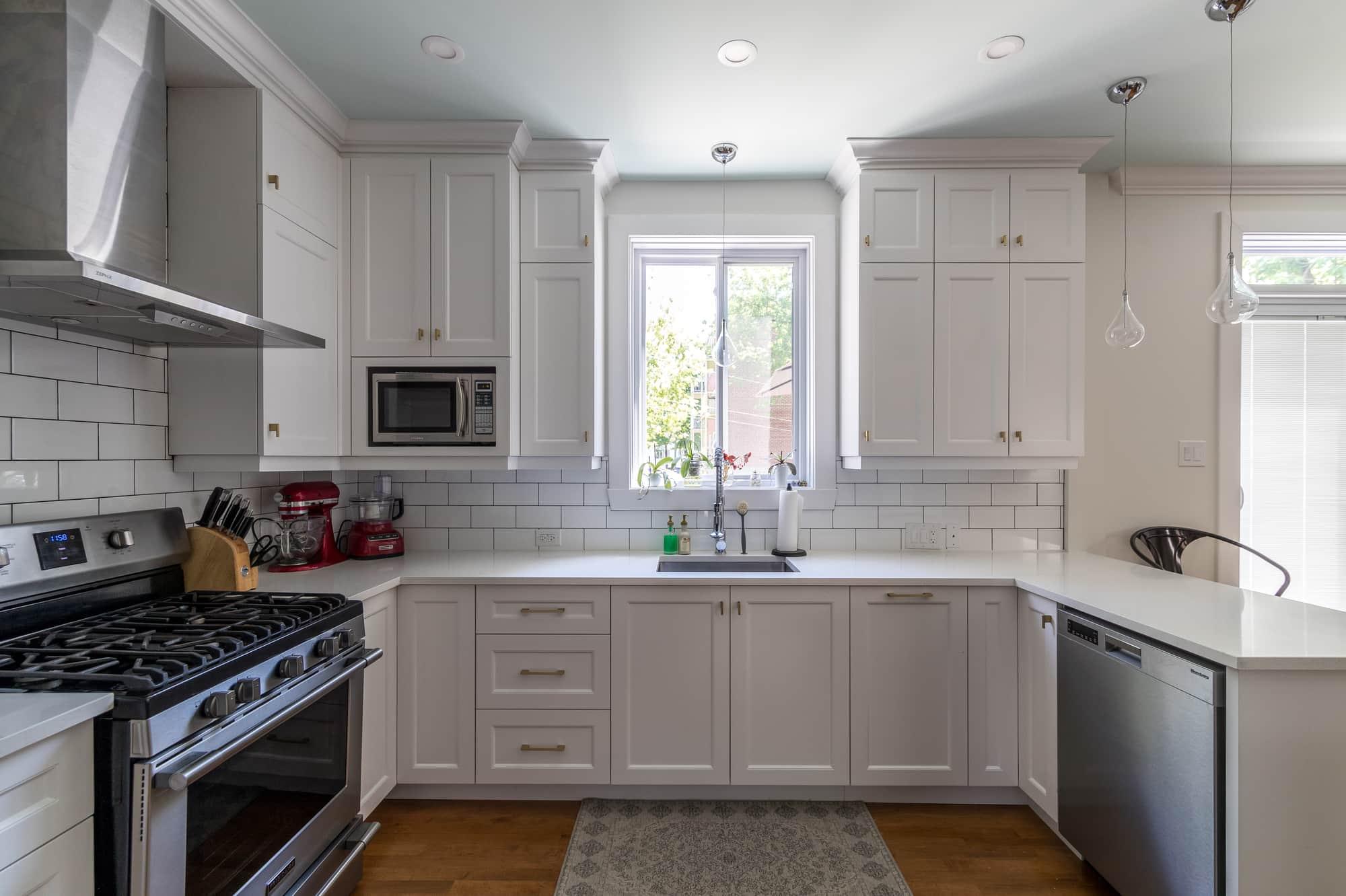 Cuisine moderne blanche avec plancher en bois franc et comptoir en quartz