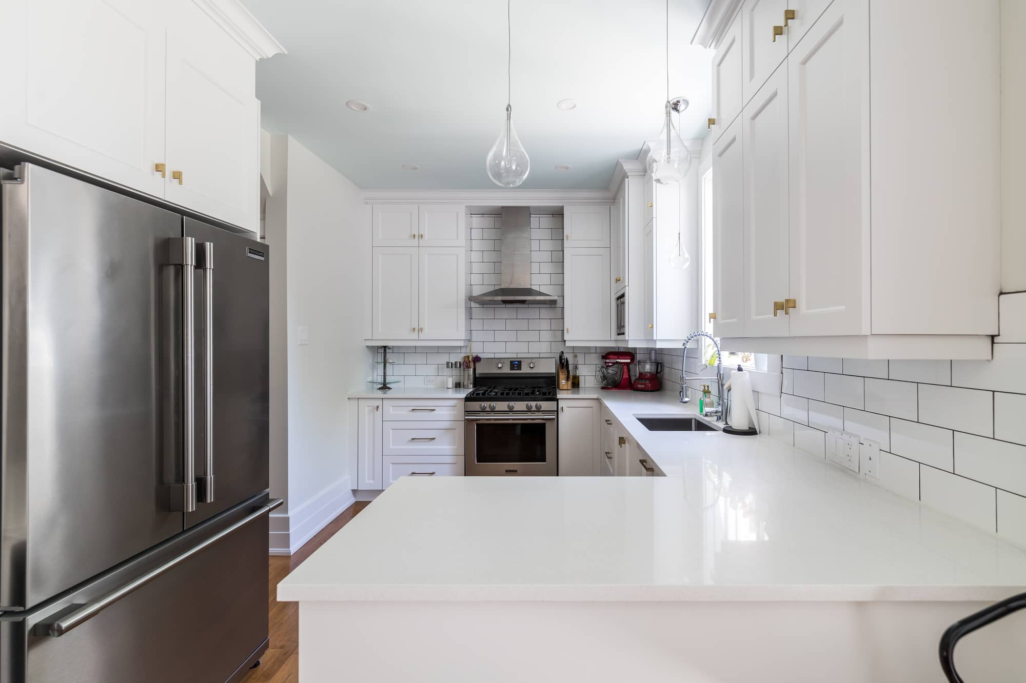 Kitchen renovation with white cabinets and stainless steel refrigerator