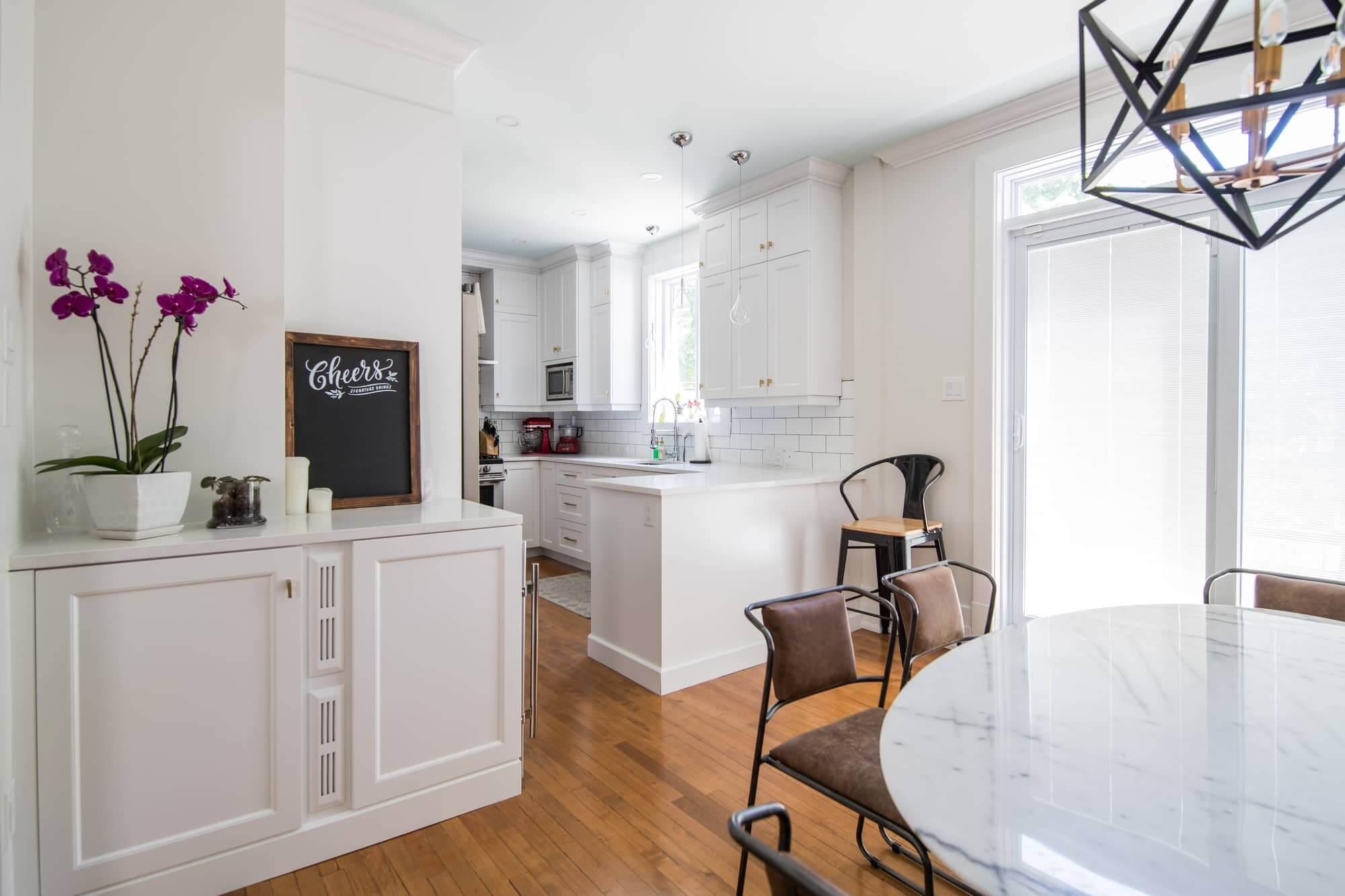 Meuble sur mesure blanc adjacent à une cuisine et salle à manger avec table en marbre