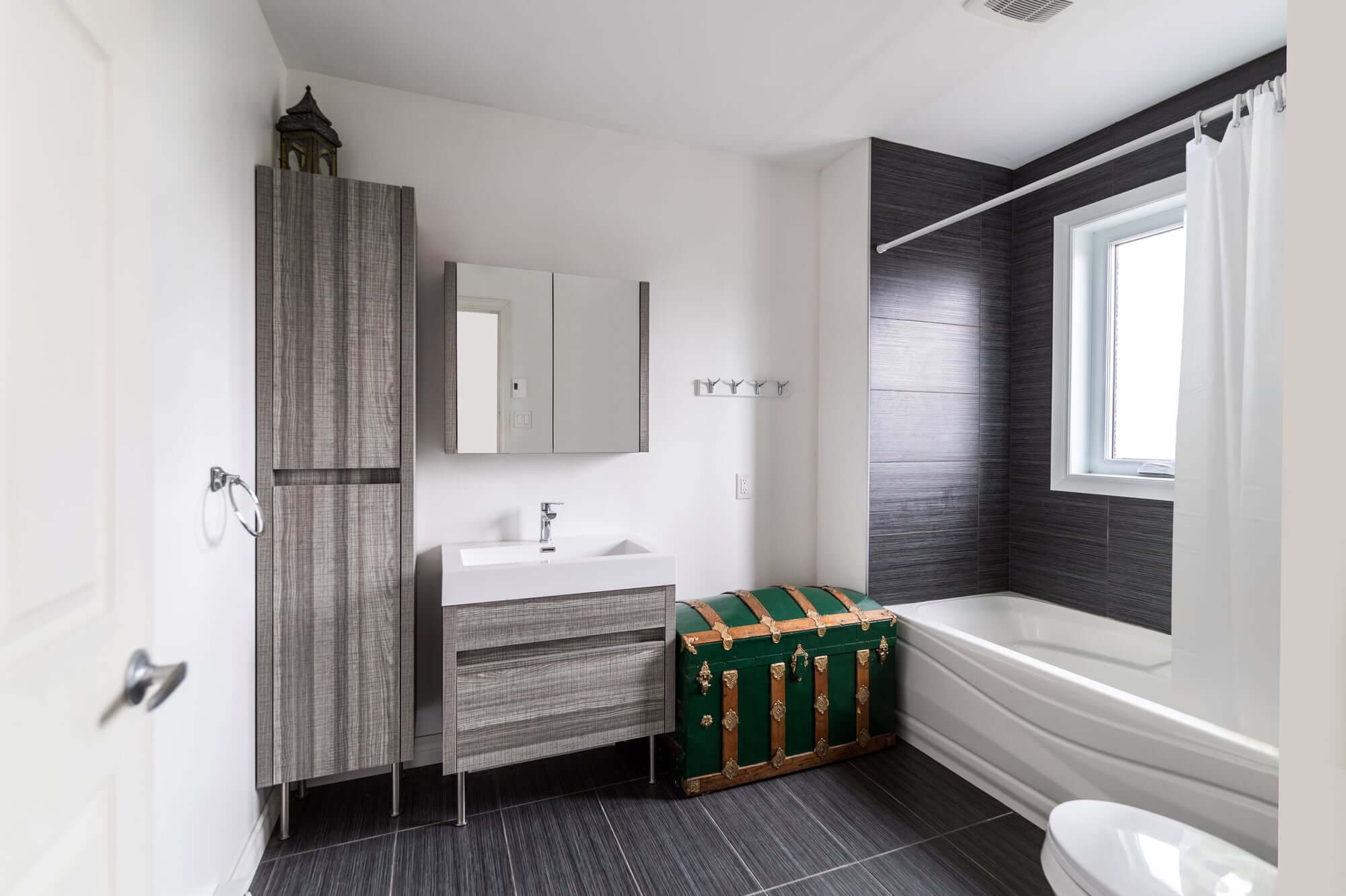 A modern bathroom with grey ceramic tiles, white walls, a shower bath and a freestanding vanity