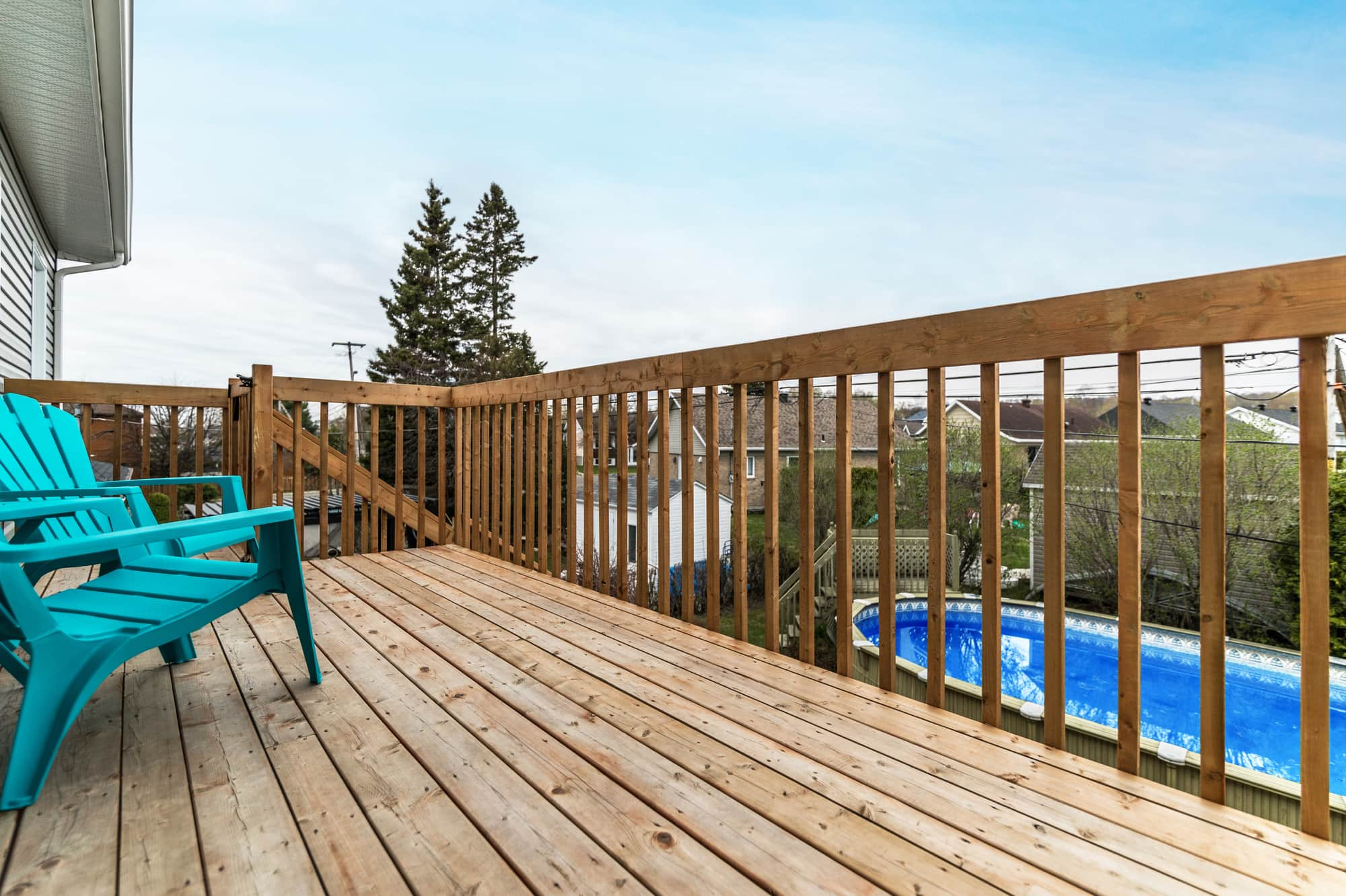 A wood balcony with two turquoise chairs