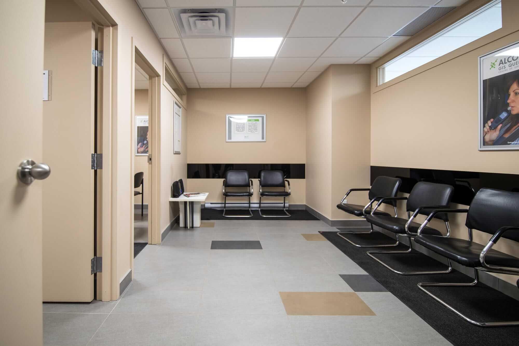 Aménagement de locaux - Vue sur salle d'attente avec chaises noires et murs beiges