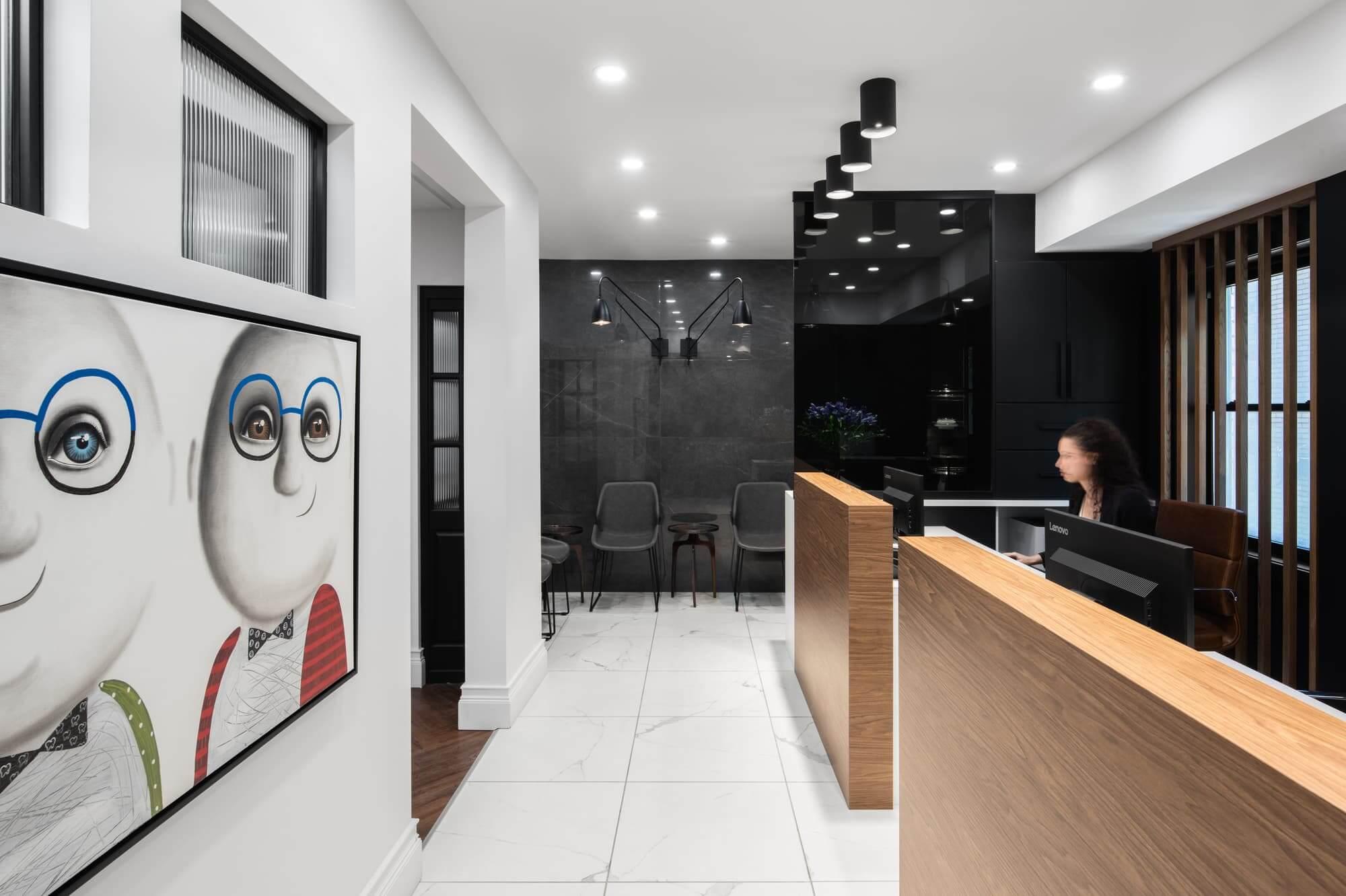 Réception d'une clinique dentaire à Montréal avec comptoirs en bois pâle, céramique style marbre et oeuvre d'art - aménagement commercial