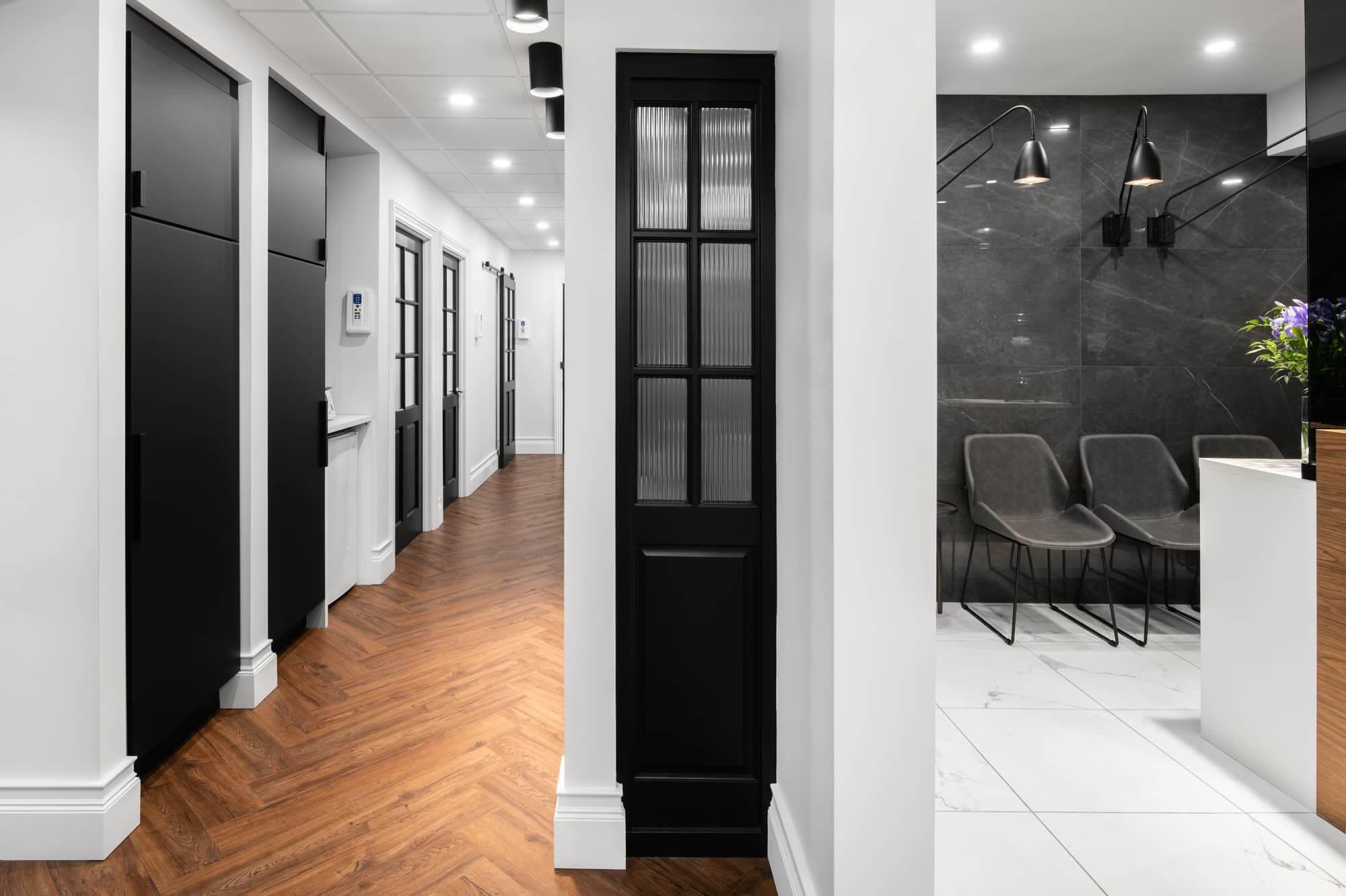 Design corridor clinique dentaire avec plancher à chevrons et portes en bois noir