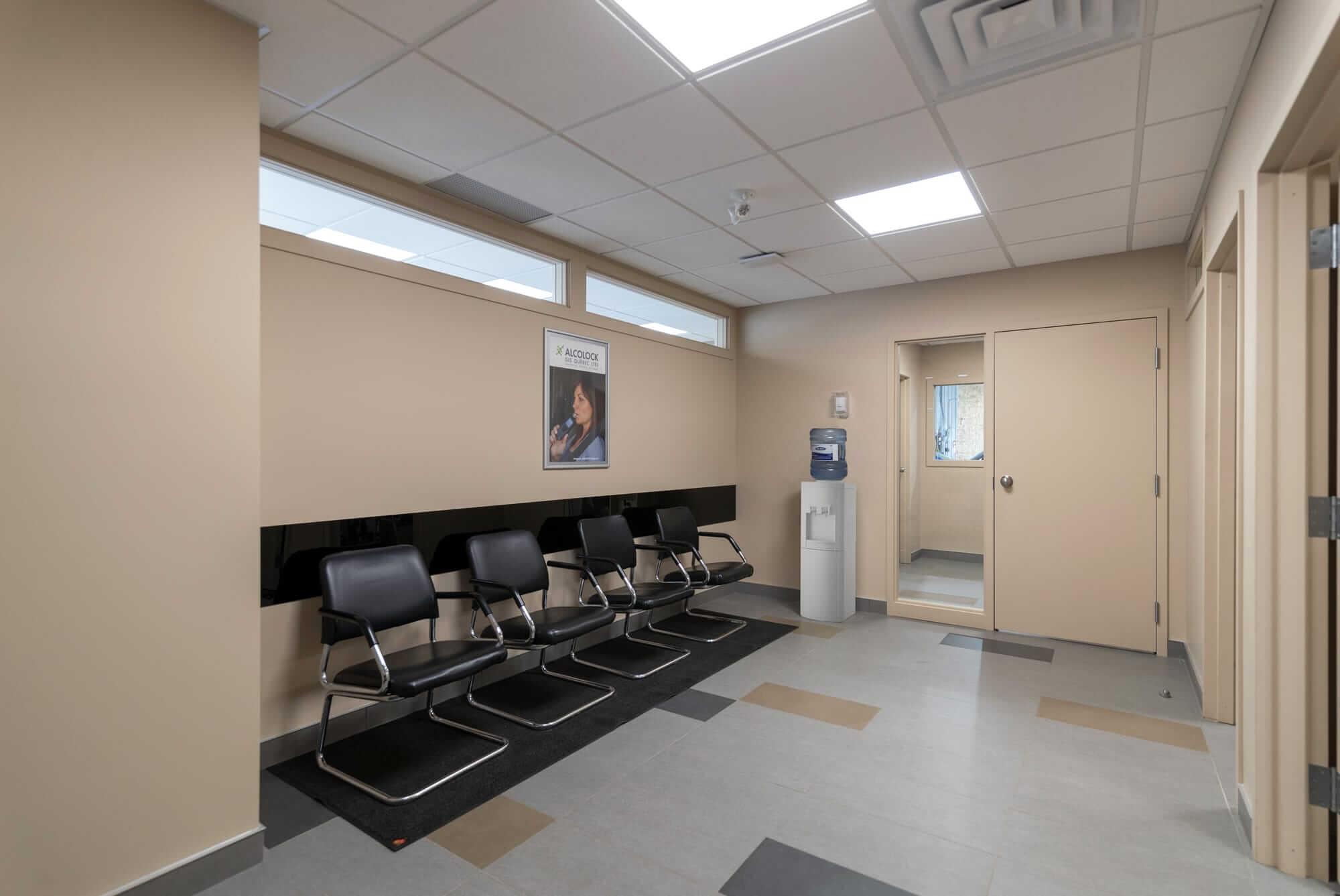 local commercial nouvellement rénové - vue sur salle d'attente avec chaises noires et murs beiges